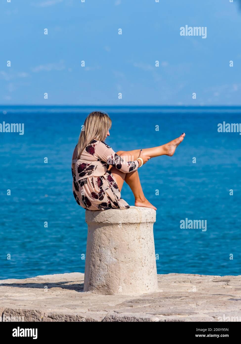 Young woman sitting on stone marine maritime harbor harbour bollard barefoot Stock Photo
