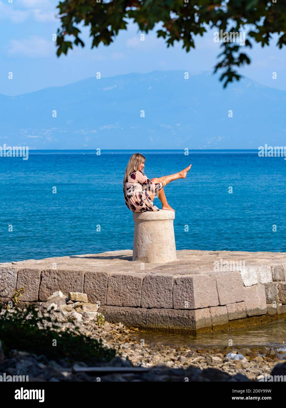 Young woman sitting on stone marine maritime harbor harbour bollard Stock Photo