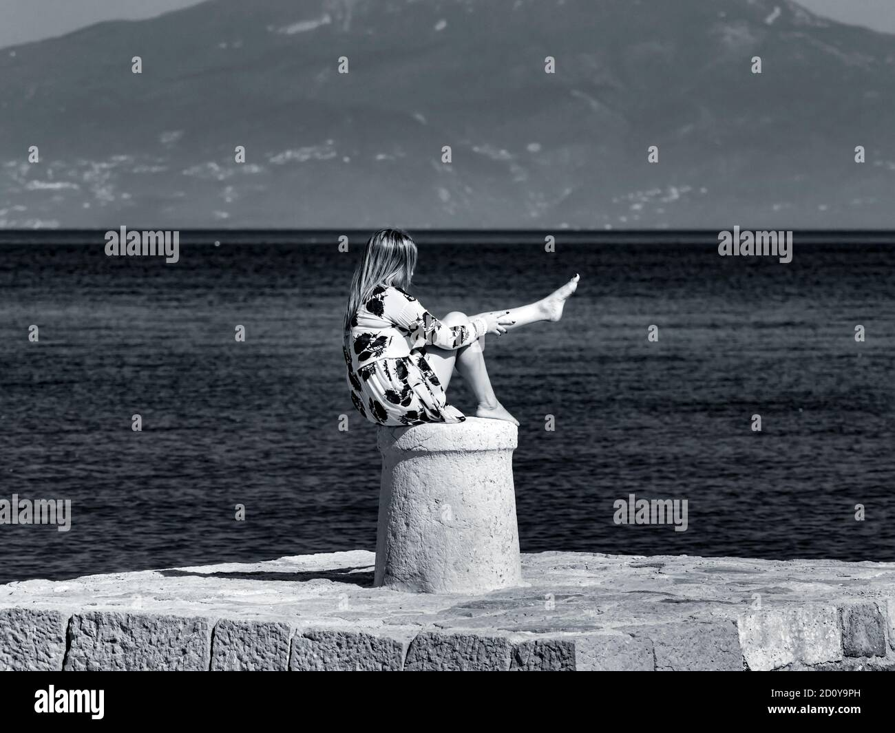 Young woman horizontal retro monochrome b&w Black and White sitting on stone marine maritime harbor harbour bollard Stock Photo