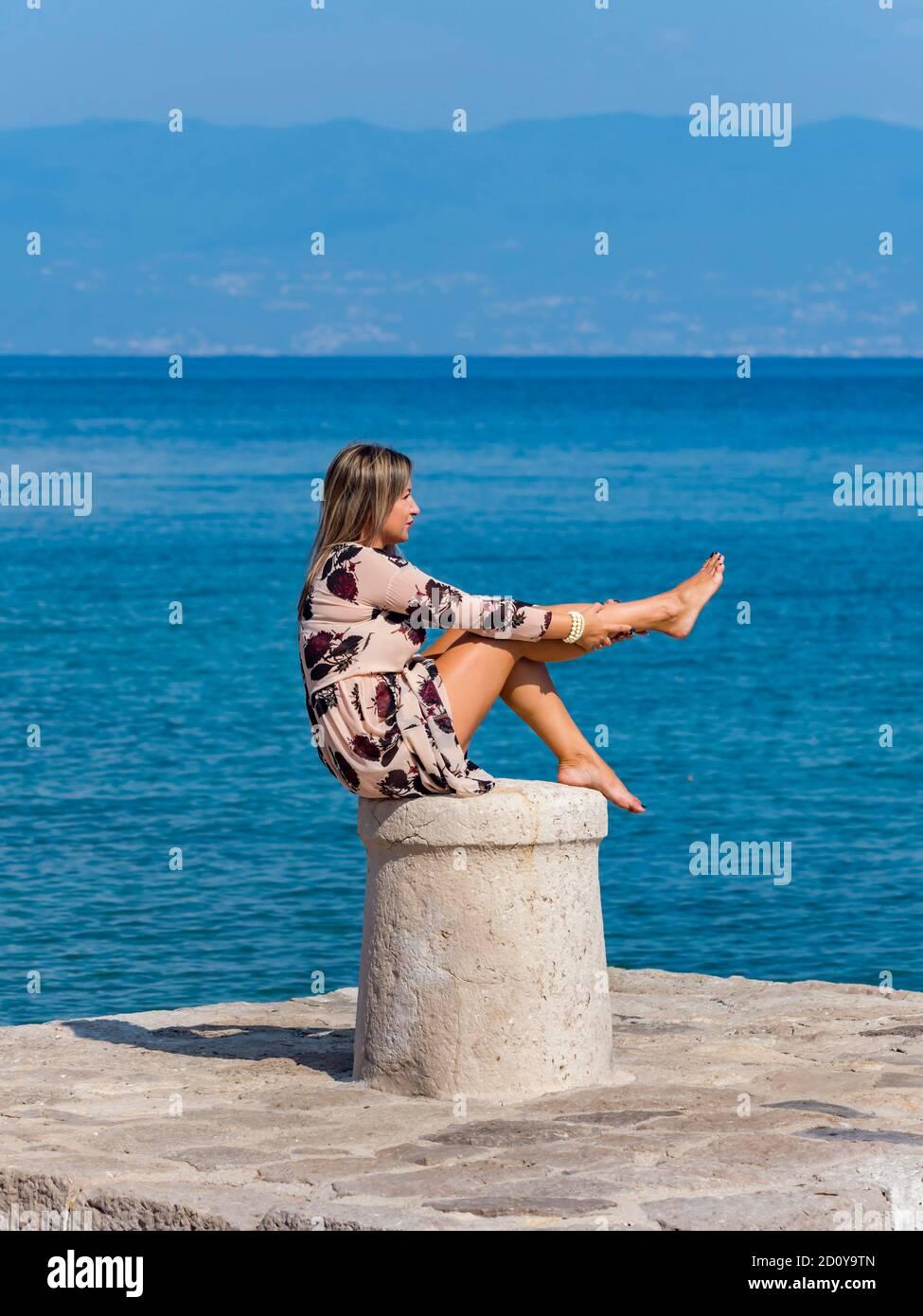 Young woman sitting on stone marine maritime harbor harbour bollard Stock Photo