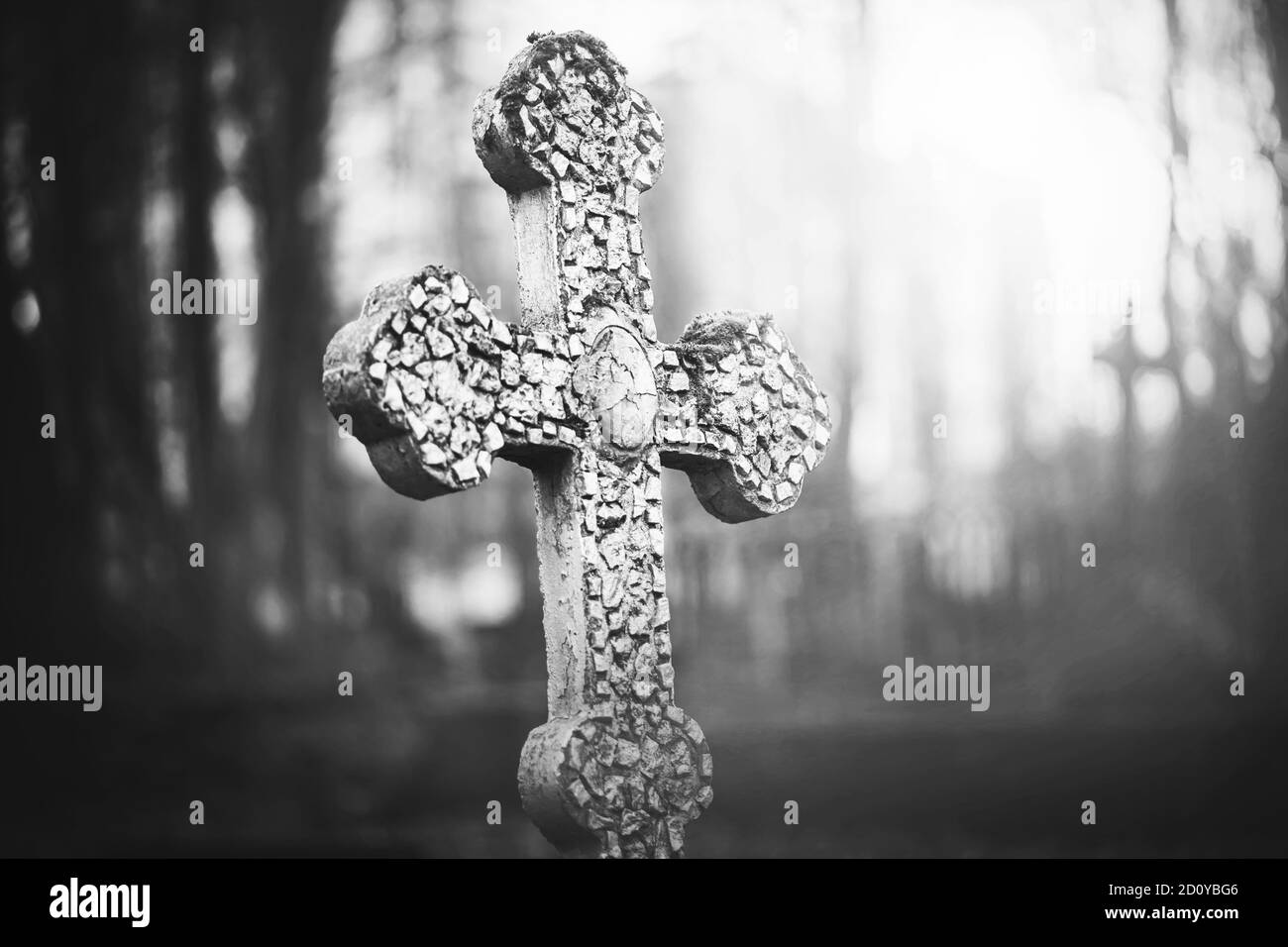A black-and-white image of an old stone cracked cross standing in the middle of a foggy abandoned scary cemetery. Sadness. Death. Stock Photo
