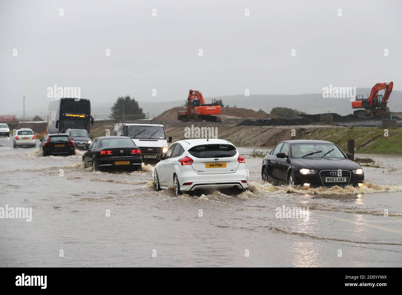 Cars make their way through a flooded road in Claudy, County Londonderry. The UK's wet weekend will continue as a weather warning for rain across parts of Wales and England has been extended. Stock Photo
