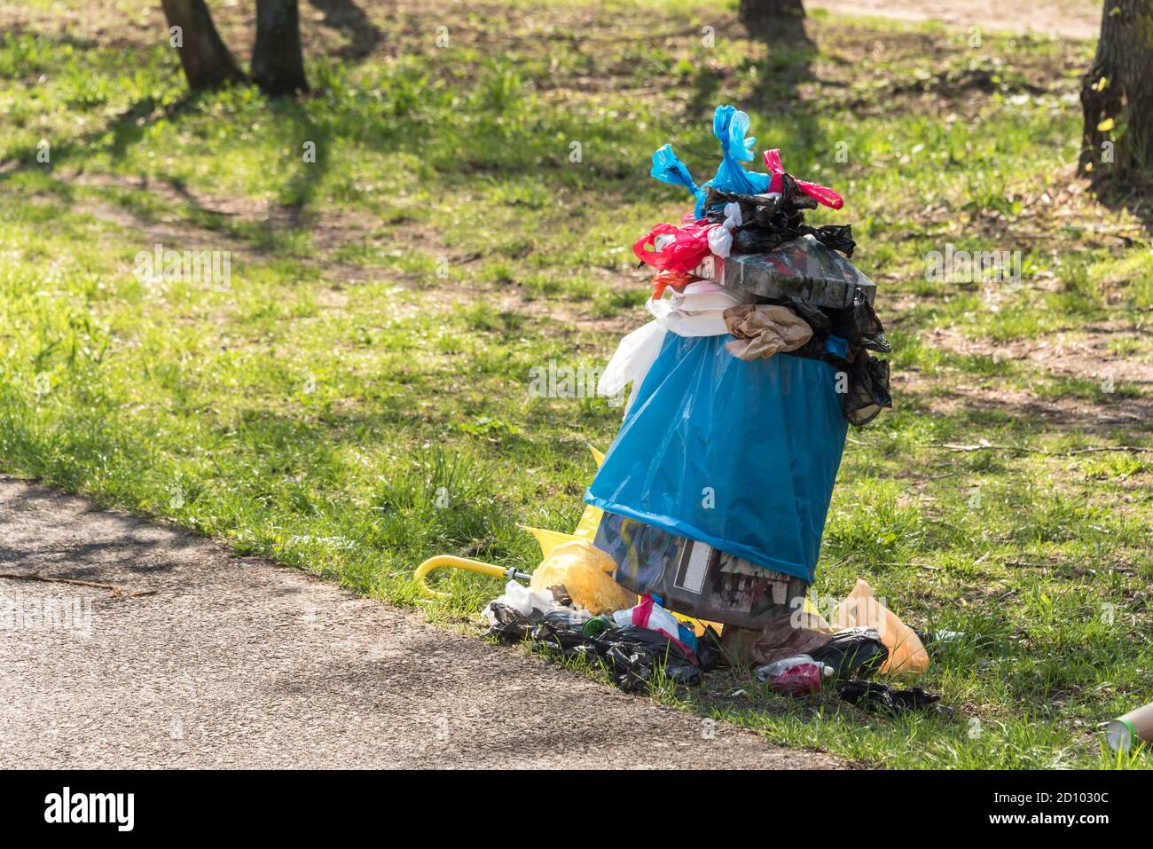 Overfull rubbish bin in park - waste, plastic bags, dog poo, messy Stock Photo