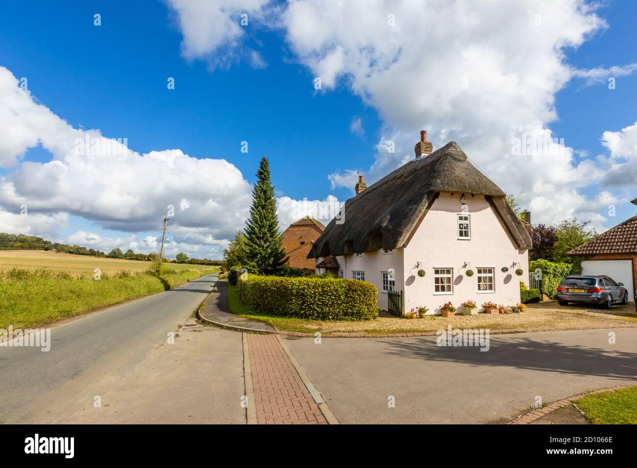 A thatched pink cottage on a rural country lane by open fields in Great Bedwyn, a village in east Wiltshire, southern England Stock Photo