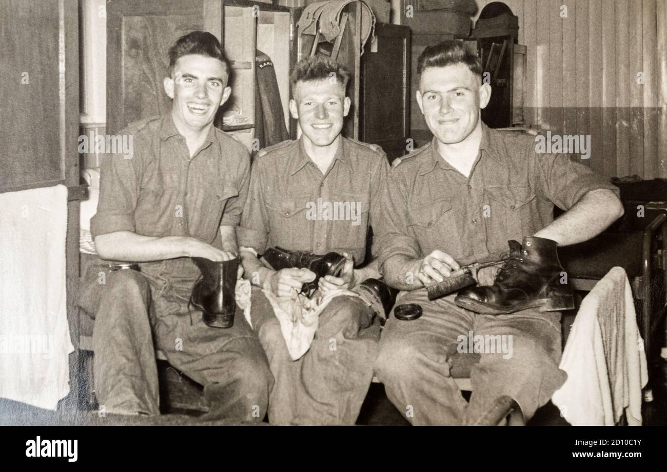 Three army recruits on National Service polishing their boots in their barracks, REME, 1956, Ash Vale, Surrey, England, UK Stock Photo