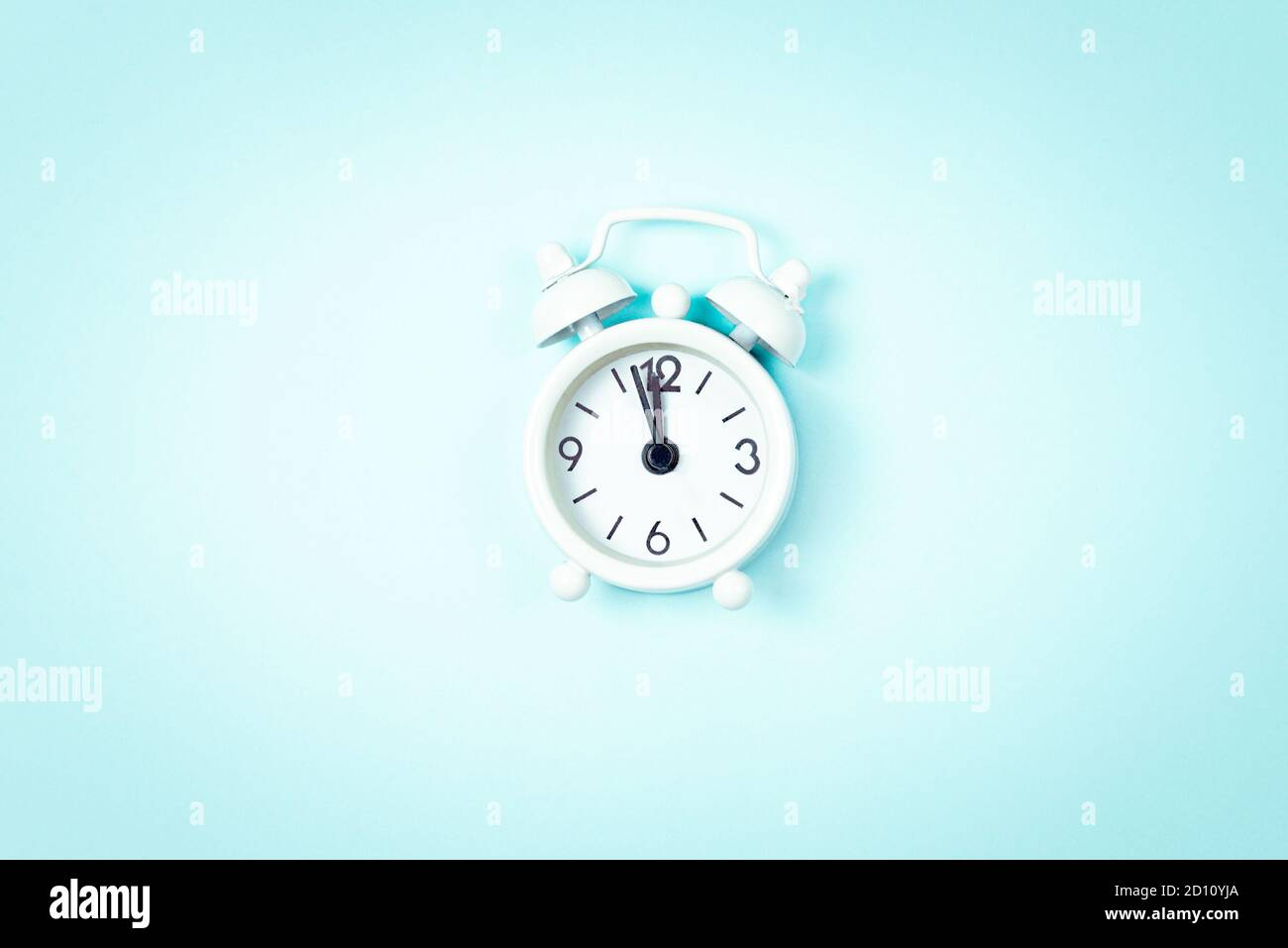 White vintage style alarm clock showing five minutes left untill midnight over blue background. New Year advent. Stock Photo