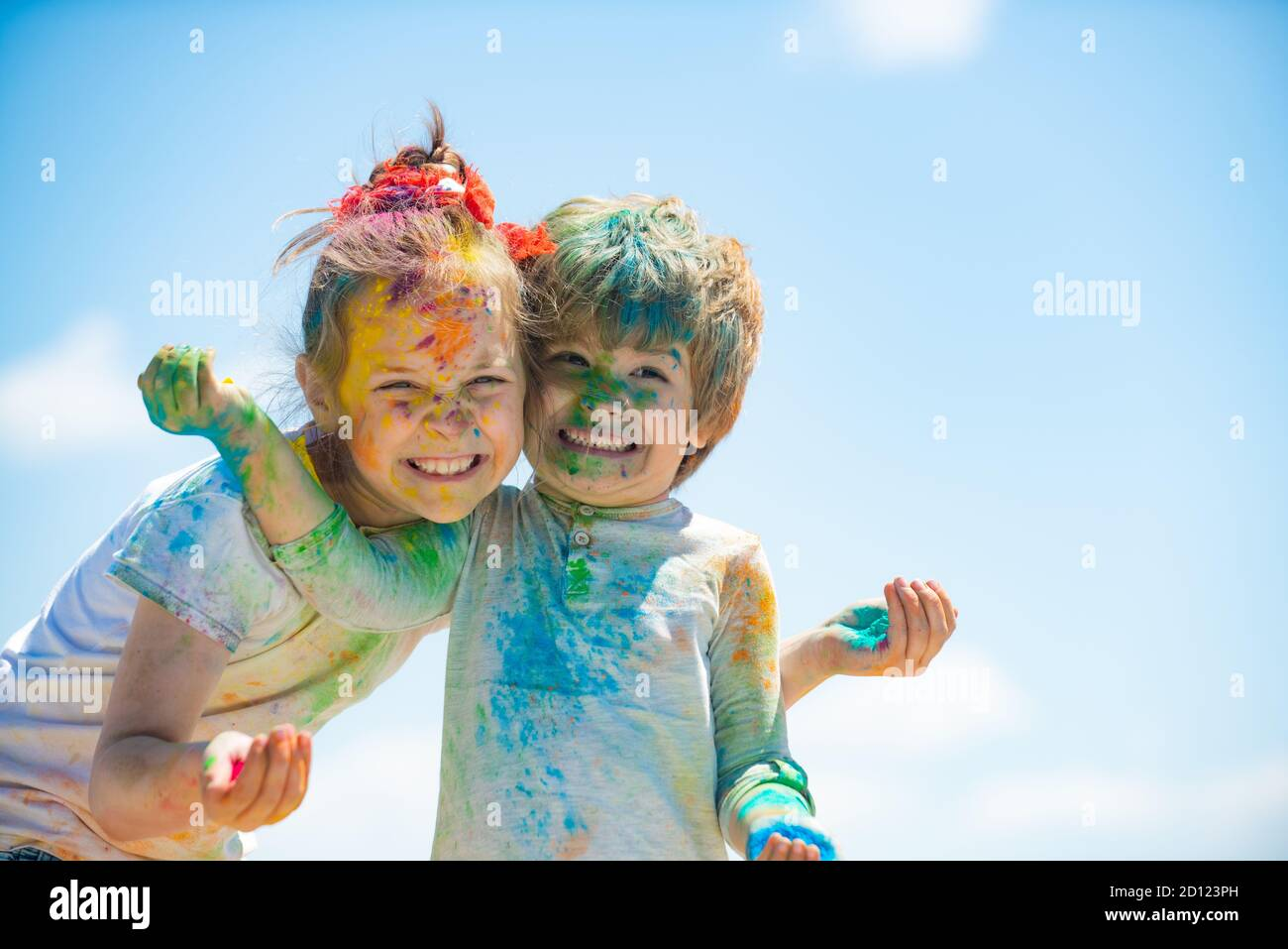 Happy childhood. Kids playing colours with smeared face. Holi festival of colors. Child girls and boy celebrate holi festival with colorful paint Stock Photo