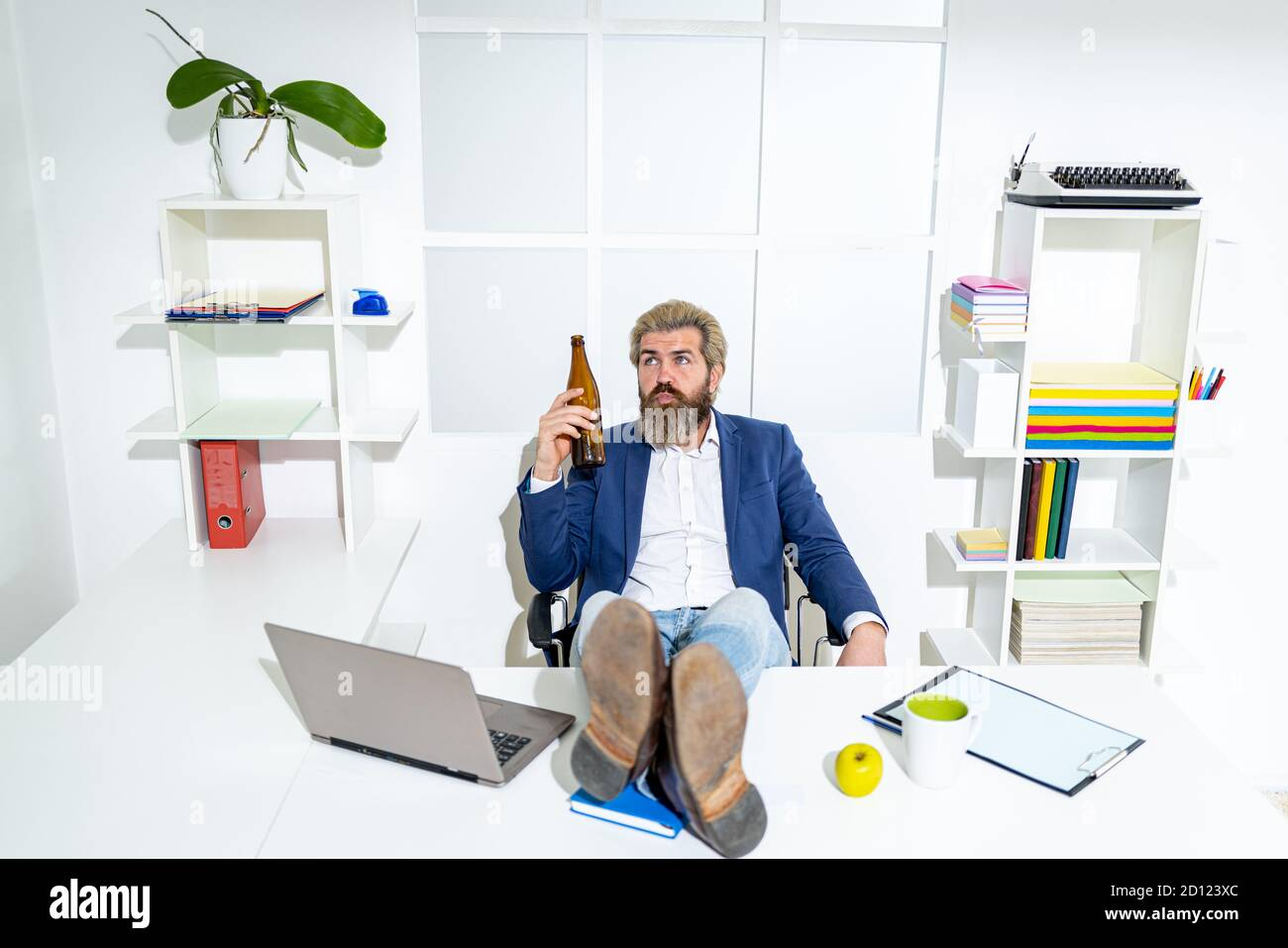Sad office worker desperate about unfair dismissal losing job. After hard work. Businessman hold a beer bottle. Stock Photo