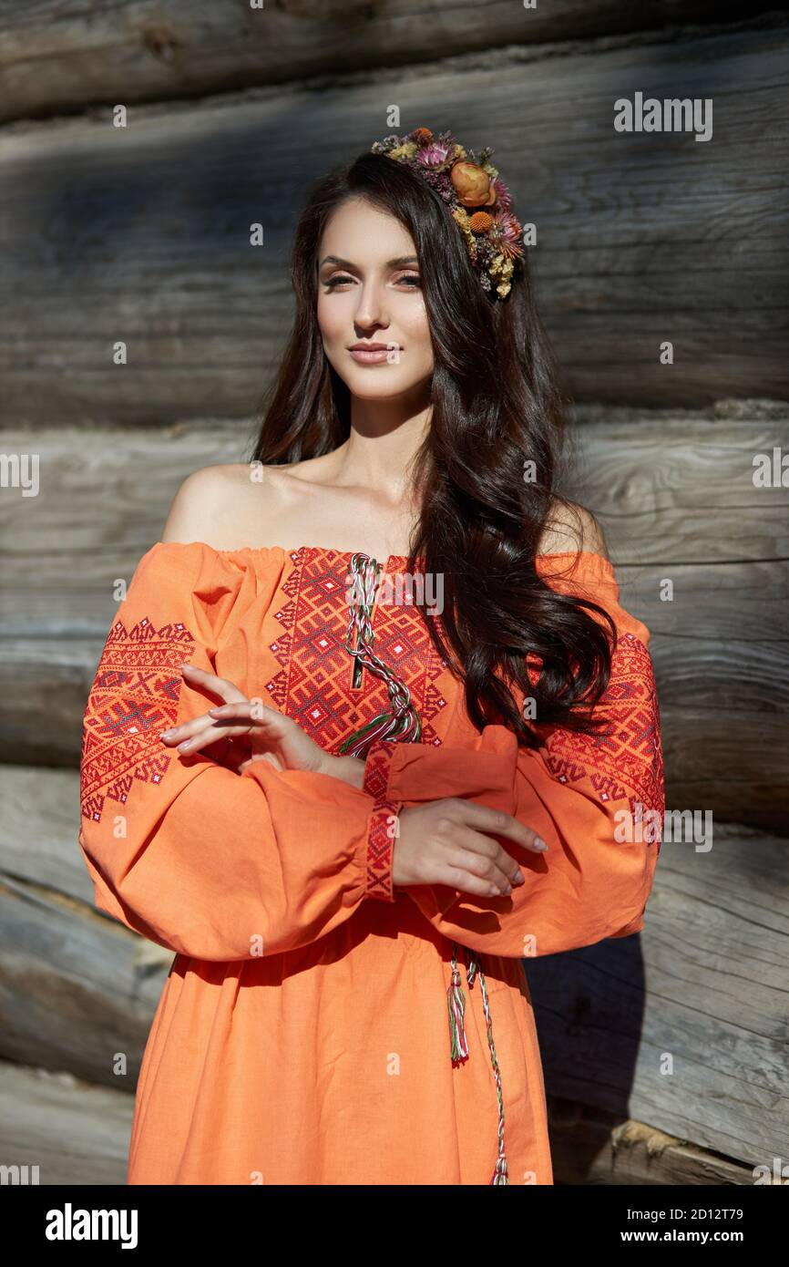 https://c8.alamy.com/comp/2D12T79/beautiful-slavic-woman-in-an-orange-ethnic-dress-and-a-wreath-of-flowers-on-her-head-beautiful-natural-makeup-portrait-of-a-russian-girl-2D12T79.jpg