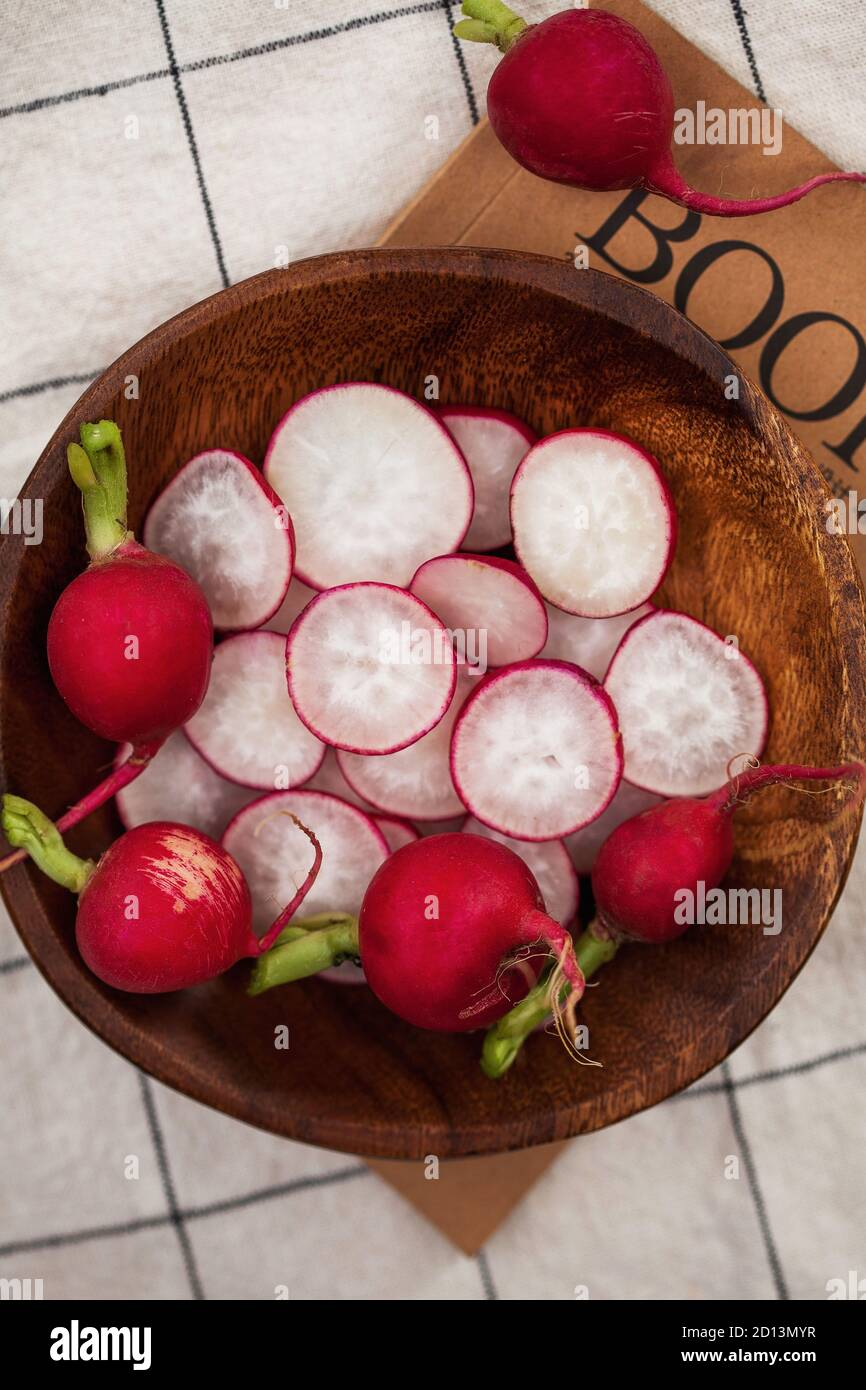 Red radish whole and cut into slices on a wooden plate against a checkered tablecloth. Food photo for ecomarket. Stock Photo