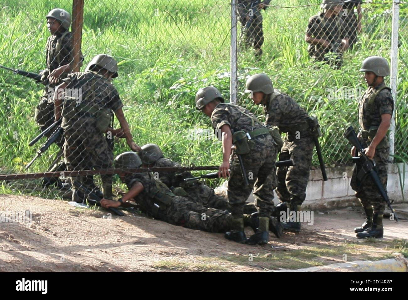 Soldiers crawl through a hole in the fencing to enter the presidential residency in Tegucigalpa June 28, 2009. Witnesses said Honduras' President Manuel Zelaya was detained at home by troops in a constitutional crisis over his attempt to win re-election. CNN's Spanish-language channel later quoted Costa Rican officials as saying he was in Costa Rica and seeking political asylum. REUTERS/Edgard Garrido (HONDURAS CONFLICT MILITARY POLITICS IMAGES OF THE DAY) Stock Photo