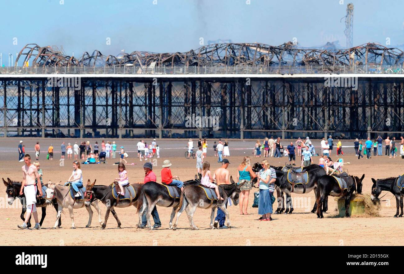 Holiday makers ride donkeys on the beach near the Grand Pier at Weston-Super-Mare in south west England July 28, 2008. Firefighters were called to a large blaze that swept through the historic pier at the Somerset seaside resort of Weston-super-Mare on Monday, police said. Flames and thick black smoke engulfed the structure and could be seen from the M5 motorway, several miles from the coast, a fire brigade spokeswoman said.   REUTERS/Toby Melville    (BRITAIN) Stock Photo
