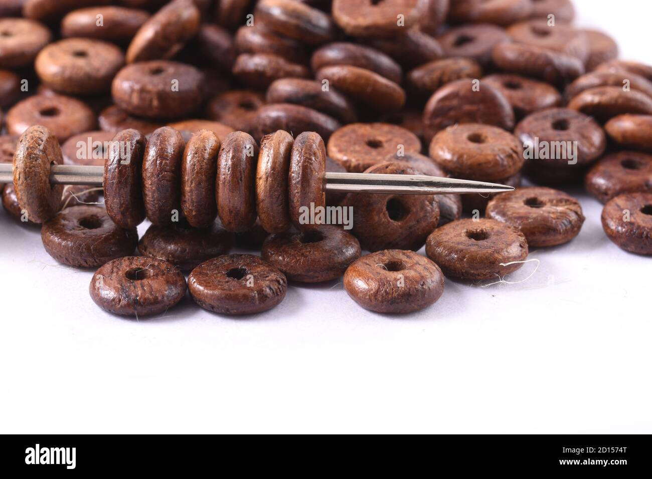 Wooden beads spread on white background with needle. Beads with needle . Close up, macro. Stock Photo