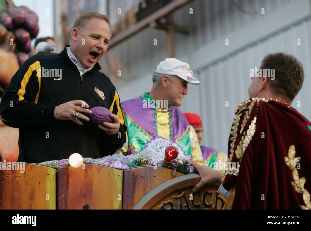 Louisiana State University national champion football head coach Les Miles (L) signs a football for a crew member during the Bacchus Mardi Gras parade in New Orleans, Louisiana February 3, 2008. REUTERS/Lee Celano (UNITED STATES) Stock Photo