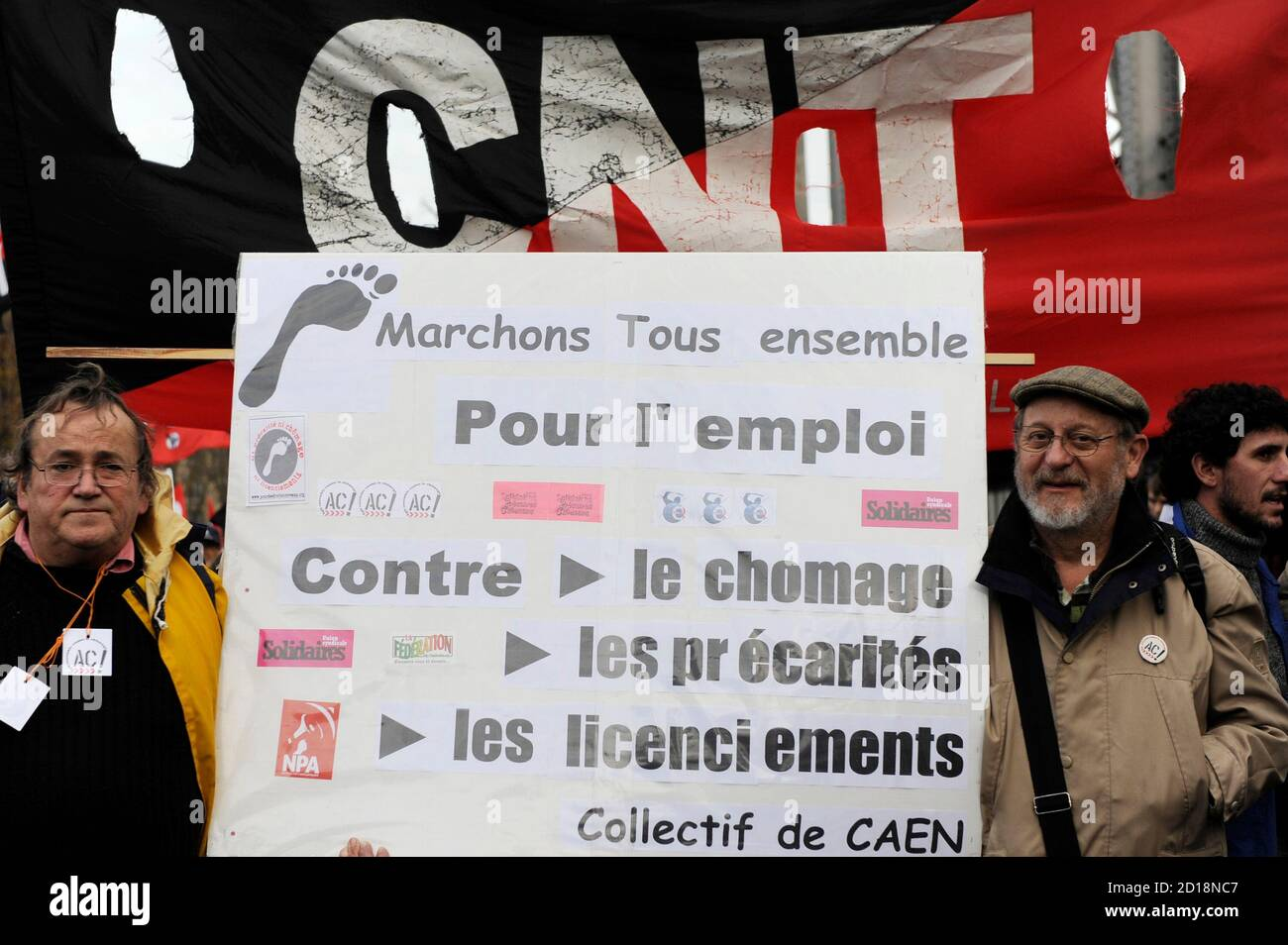 """Men carrying a sign which reads: """"Let's walk together for employment: against unemployment, job insecurity and layoffs."""", attend a national demonstration to protest against unemployment in Paris December 5, 2009. REUTERS/Gonzalo Fuentes (FRANCE POLITICS CONFLICT EMPLOYMENT BUSINESS) Stock Photo"""