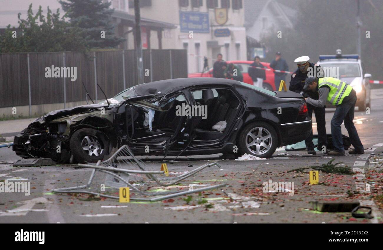 Austrian policemen stand next to the wreckage of the car of the leader of Austria's Buendnis Zukunft Oesterreich (BZOe) party (Alliance for Austria's future) Joerg Haider in the village of Lambichl, near the Carinthian capital Klagenfurt, October 11, 2008. Haider was killed in a car accident on Saturday near his home town of Klagenfurt, police said. The 58-year-old governor of Austria's Carinthia province died after suffering major head and chest injuries when the government car he was driving went out of control and rolled down an embankment, police said. Police said they were investigating t Stock Photo