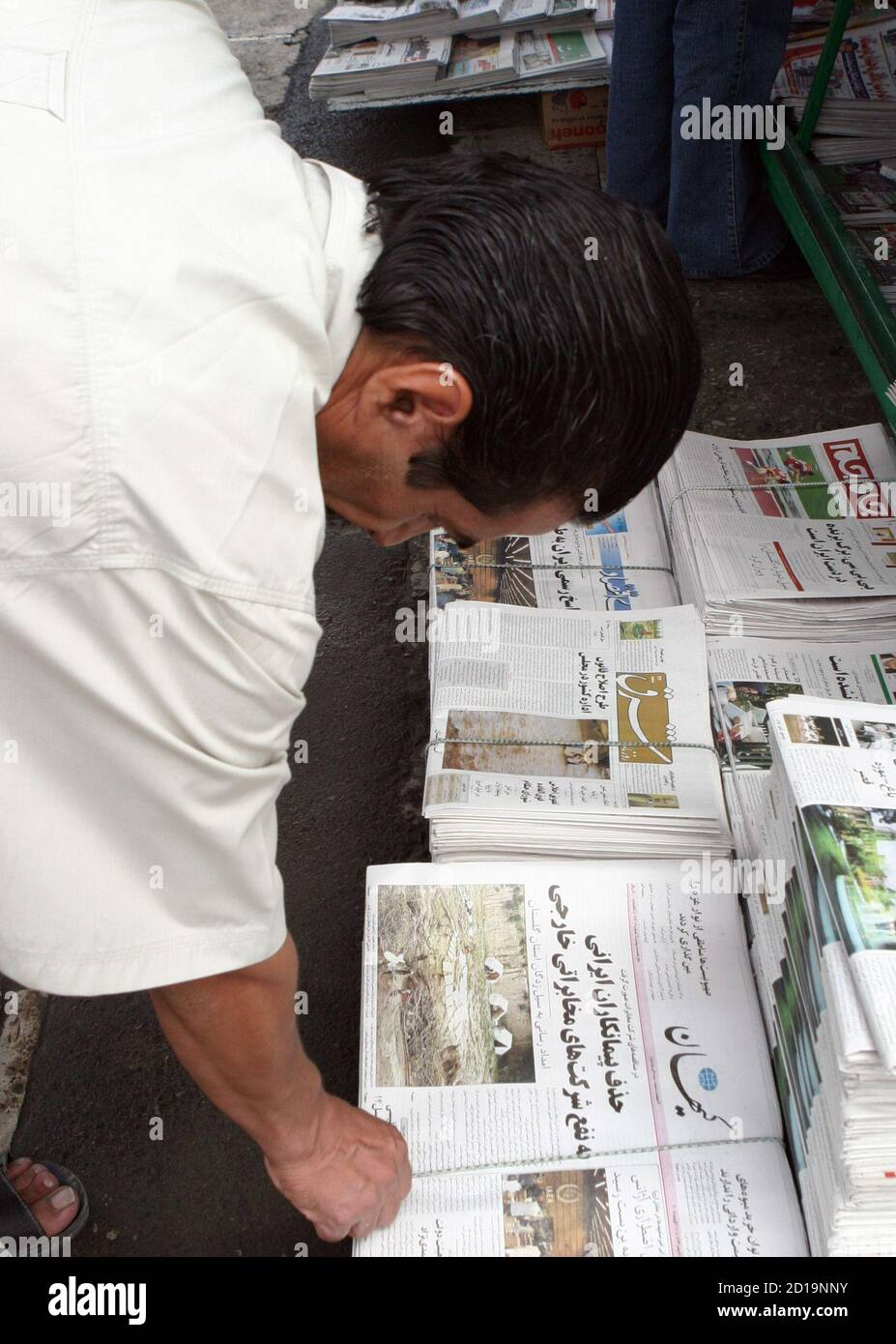 An Iranian man reads newspapers at a newsstand in Tehran august 11, 2005. Iran began breaking U.N. seals at a uranium processing plant on August 10th, U.N. and Iranian officials said, a step on the road to production of enriched uranium that could be used for nuclear weapons. 'They have begun breaking the seals,' International Atomic Energy Agency (IAEA) spokesman Mark Gwozdecky said. REUTERS/Raheb Homavandi  CJF/RH/LA Stock Photo
