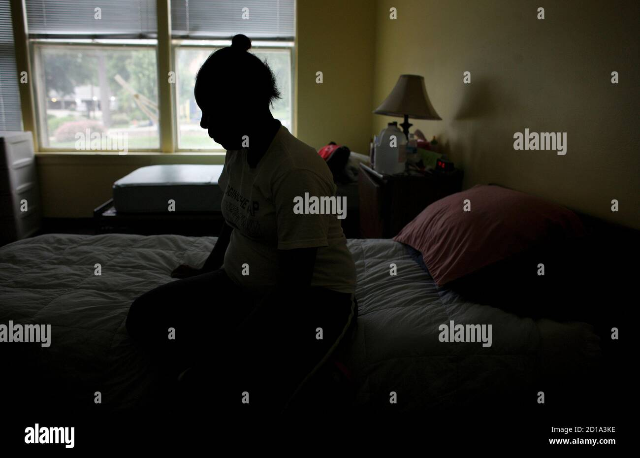 EDITOR'S NOTE: SUBJECT IS SILHOUETTED TO PROTECT HER IDENTITY FOR HER SAFETY, THIS IMAGE SHOULD NOT BE LIGHTENED TO SHOW SUBJECT'S FACE A pregnant victim of domestic violence rests in her room at Mutual Ground's shelter in Aurora, Illinois, June 18, 2009. Housed in a 19th century mansion, Mutual Ground Inc shelter for battered women and children which last year housed 400 people is now another victim of the crisis in U.S. social services amid a deep recession and plans to close its doors on July 1. Picture taken June 18, 2009. REUTERS/John Gress (UNITED STATES CONFLICT  BUSINESS SOCIETY IMAGES Stock Photo