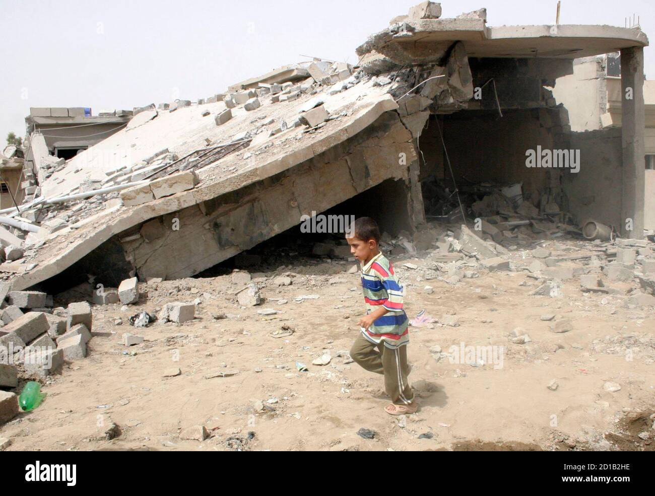 A boy runs past a damaged house after a bomb attack in Mosul, 390 km (242 miles) north of Baghdad July 9, 2009. Two car bombs exploded within minutes of each other on Wednesday in the northern Iraqi city of Mosul, killing 14 people and wounding 33, police said. REUTERS/Khalid al-Mousuly (IRAQ CONFLICT) Stock Photo