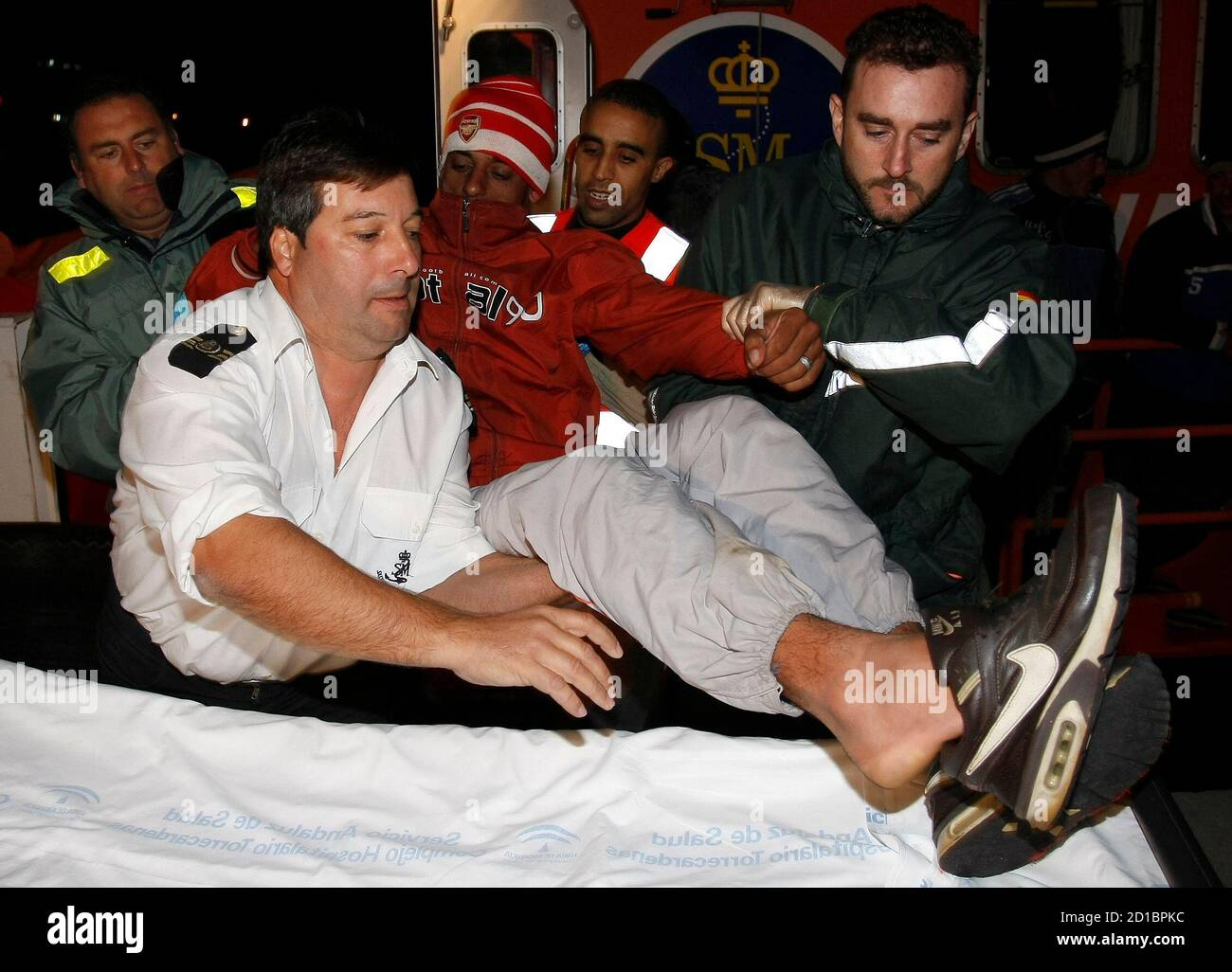 A would-be immigrant is carried by members of the Spanish Civil Guard and Red Cross after arriving at the port of Almeria November 16, 2007. They were intercepted off the southern Spanish coast as they were heading to European soil from Africa, authorities said. REUTERS/Francisco Bonilla (SPAIN) Stock Photo