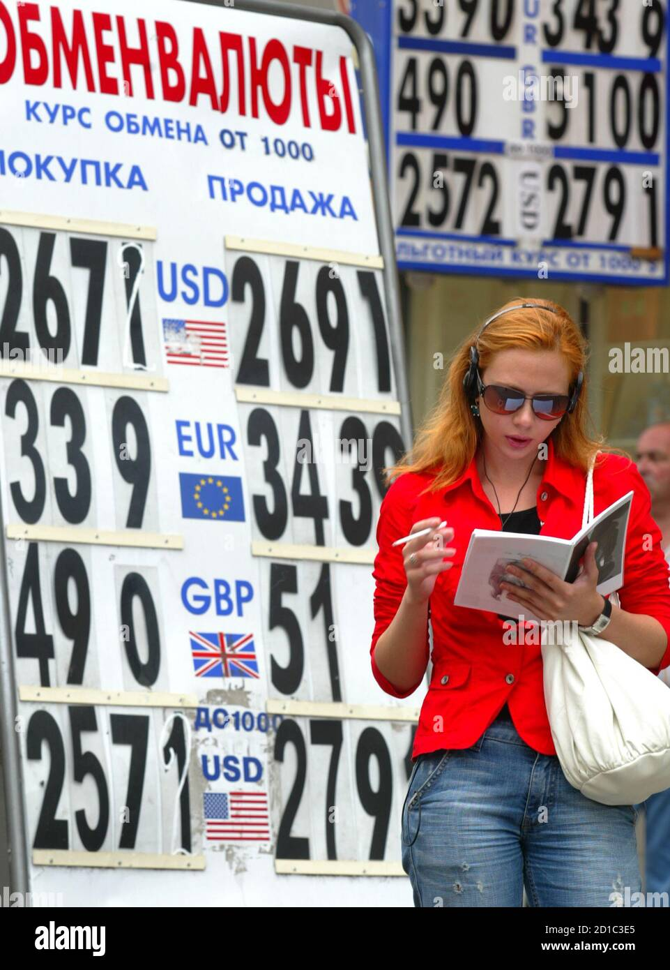 A woman reads as she stands in front of a currency exchange rate board in Moscow June 30, 2006. The many, often derogatory, names Russians have for their roubles stem from the Soviet Union, where the national currency was officially more valuable than the dollar but worthless outside its borders. From Saturday, officials hope, that age will be past. The last restrictions on the rouble will be scrapped, and it will become convertible -- a currency like the dollar or the yen.   REUTERS/Ivan Chernichkin (RUSSIA) Stock Photo