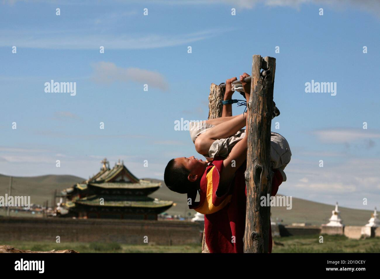 A Buddhist monk plays at the backyard of the Erdene Zeu monastery in Kharahorin, some 380 km (236 miles) west of Ulan Bator, July 8, 2006. The Erdene Zeu monastery was ransacked during the Stalinist period, and worship was forbidden throughout the Communist era, but Buddhism is experiencing a revival since Mongolia overthrew decades of Soviet dominance in 1991. Stock Photo