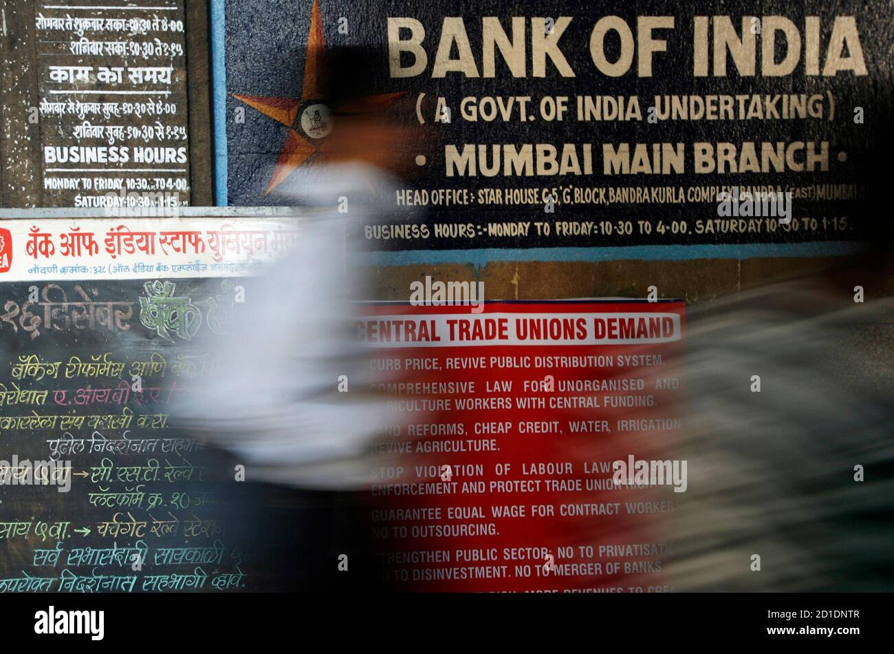 A man walks in front of a banner outside a state-run bank during a strike in Mumbai December 16, 2009. About 400,000 bank employees went on strike on Wednesday to protest merging state-owned banks, partially affecting cash transactions and clearing operations, a bank union official said. REUTERS/Arko Datta (INDIA - Tags: BUSINESS) Stock Photo