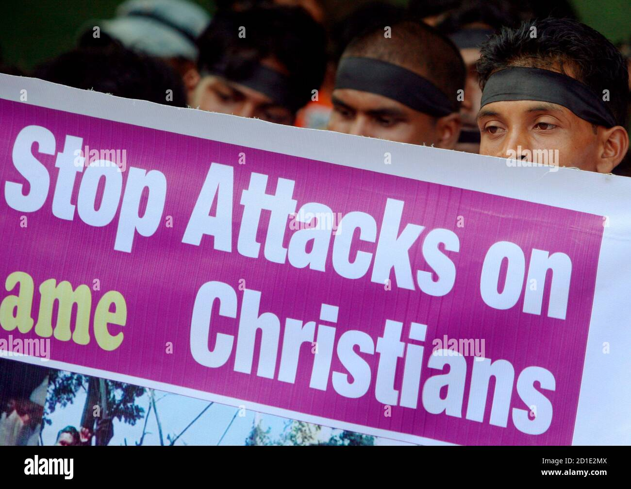 Christians hold a banner during a protest rally in Mumbai October 5, 2008, against the recent violence on Christians in Orissa. Authorities imposed a curfew in several towns in eastern India on Wednesday after fresh attacks by Hindus on Christians as clashes over religious conversions spread, officials said. A string of attacks on Christians in three states has killed at least 34 people and forced thousands to flee to government camps or hide in forests. The troubles have been sparked by controversial conversion campaigns by Christian groups in poor tribal areas.  REUTERS/Punit Paranjpe (INDIA Stock Photo