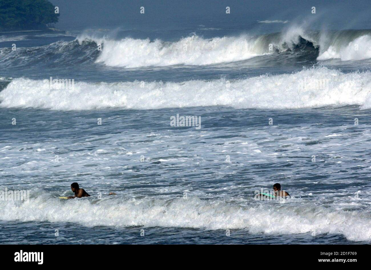Surfers play on the high waves in Kuta beach in Bali island May 19, 2007. Massive waves have hit coastlines across Indonesia, sending hundreds of panicky residents rushing from their homes and also destroying fishing boats and beachside shacks, officials and media reports said on Friday.  REUTERS/Murdani Usman  (INDONESIA) Stock Photo