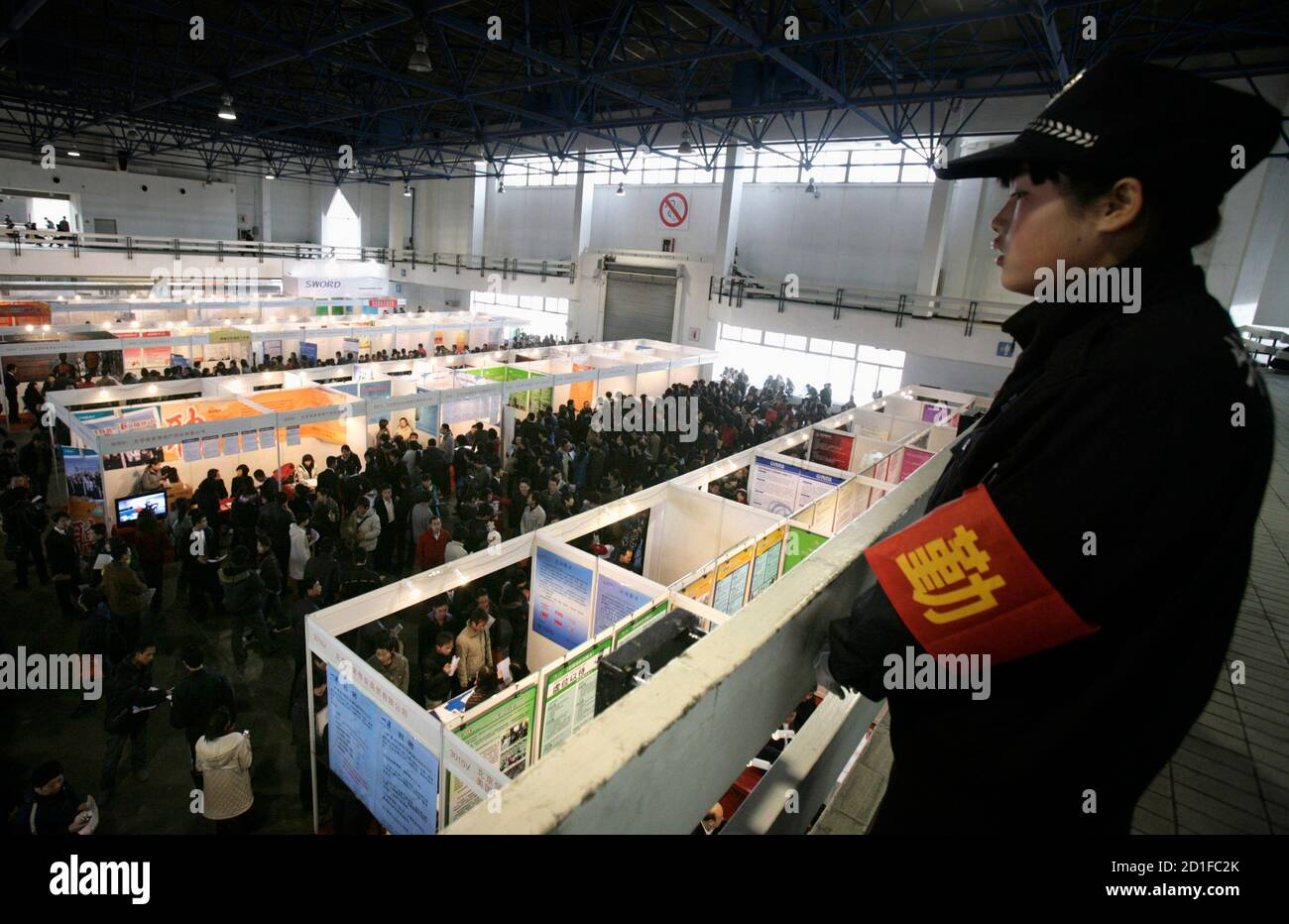 A security woman keeps order at a job fair in Beijing February 14, 2009. China must push job creation as an even higher priority in setting economic policy, the government said on Tuesday, laying down rules for employers and officials to discourage potentially volatile sackings. REUTERS/Grace Liang (CHINA) Stock Photo