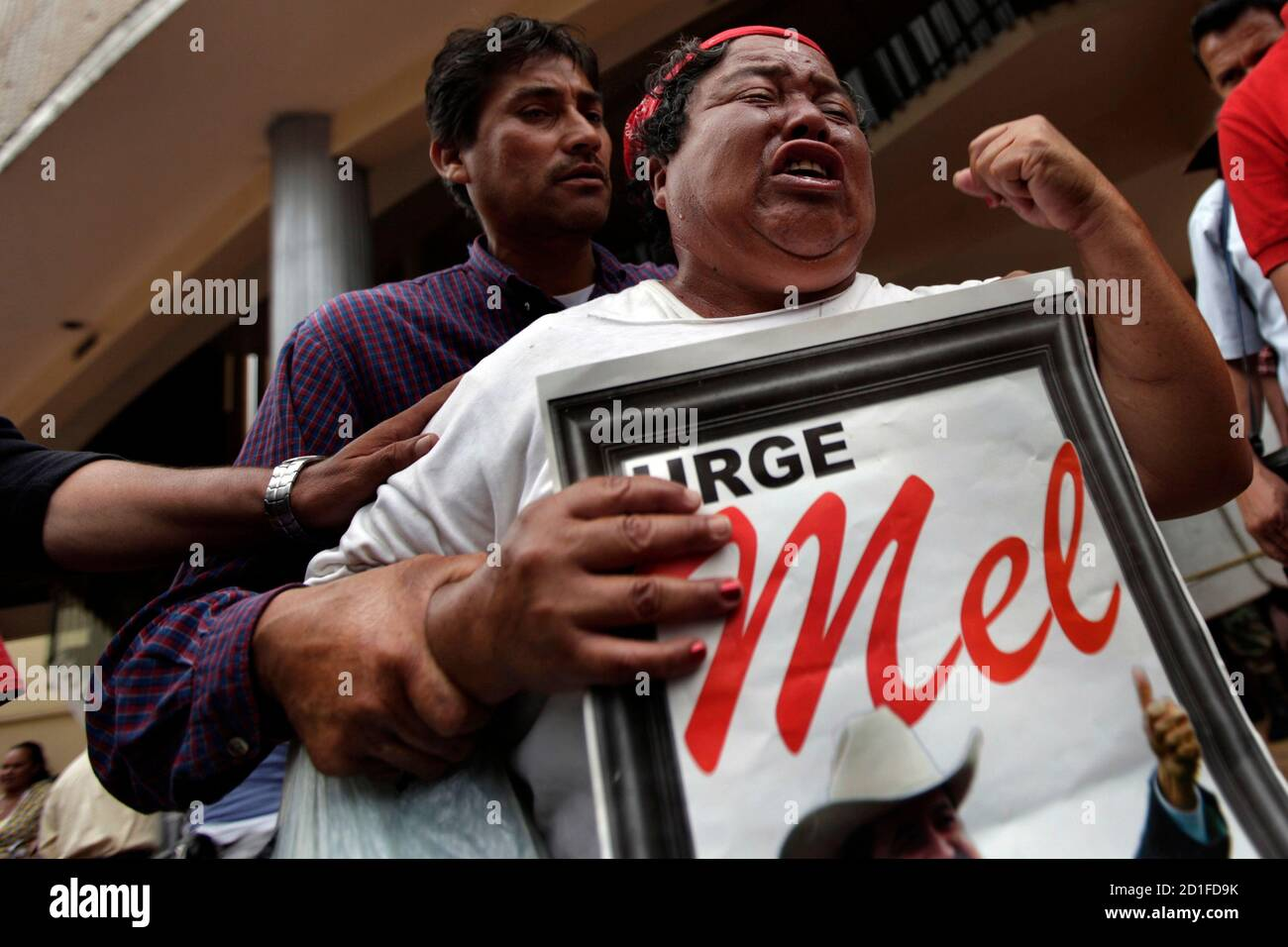 """A supporter of Honduras' ousted president Manuel Zelaya cries during a protest outside National Congress in Tegucigalpa July 15, 2009.The United States urged the rival sides in Honduras' political crisis on Tuesday to give dialogue a chance, but the deposed president is threatening to abandon talks mediated by Costa Rica if he is not reinstated quickly. A second round of talks is set for Saturday. The poster reads, """"Urge Mel"""". REUTERS/Edgard Garrido (HONDURAS) Stock Photo"""