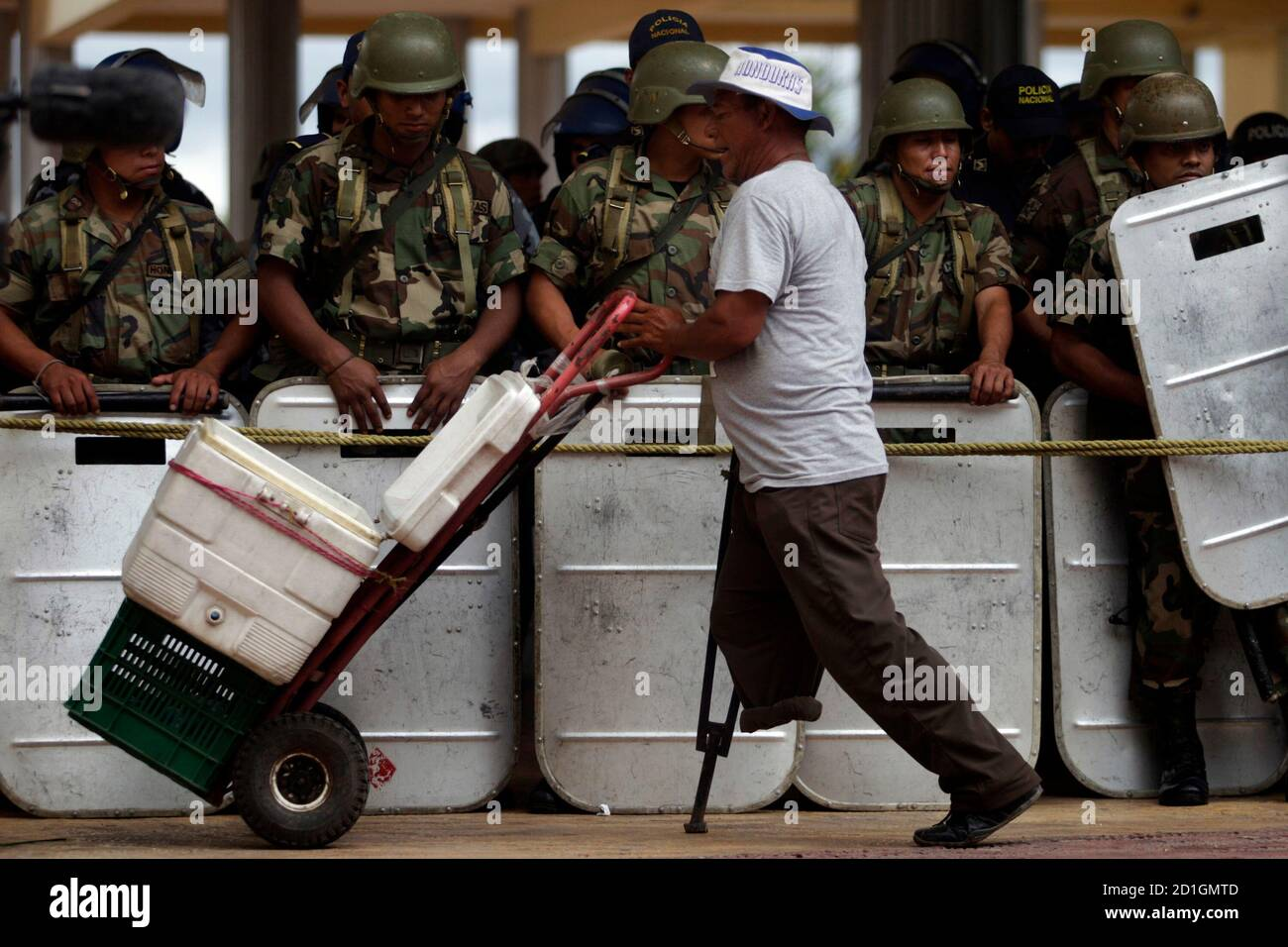 A water vendor walks in front of soldiers outside National Congress inTegucigalpa July 15, 2009. The United States urged the rival sides in Honduras' political crisis on Tuesday to give dialogue a chance, but the deposed president is threatening to abandon talks mediated by Costa Rica if he is not reinstated quickly. A second round of talks is set for Saturday REUTERS/Edgard Garrido (HONDURAS POLITICS CONFLICT MILITARY) Stock Photo