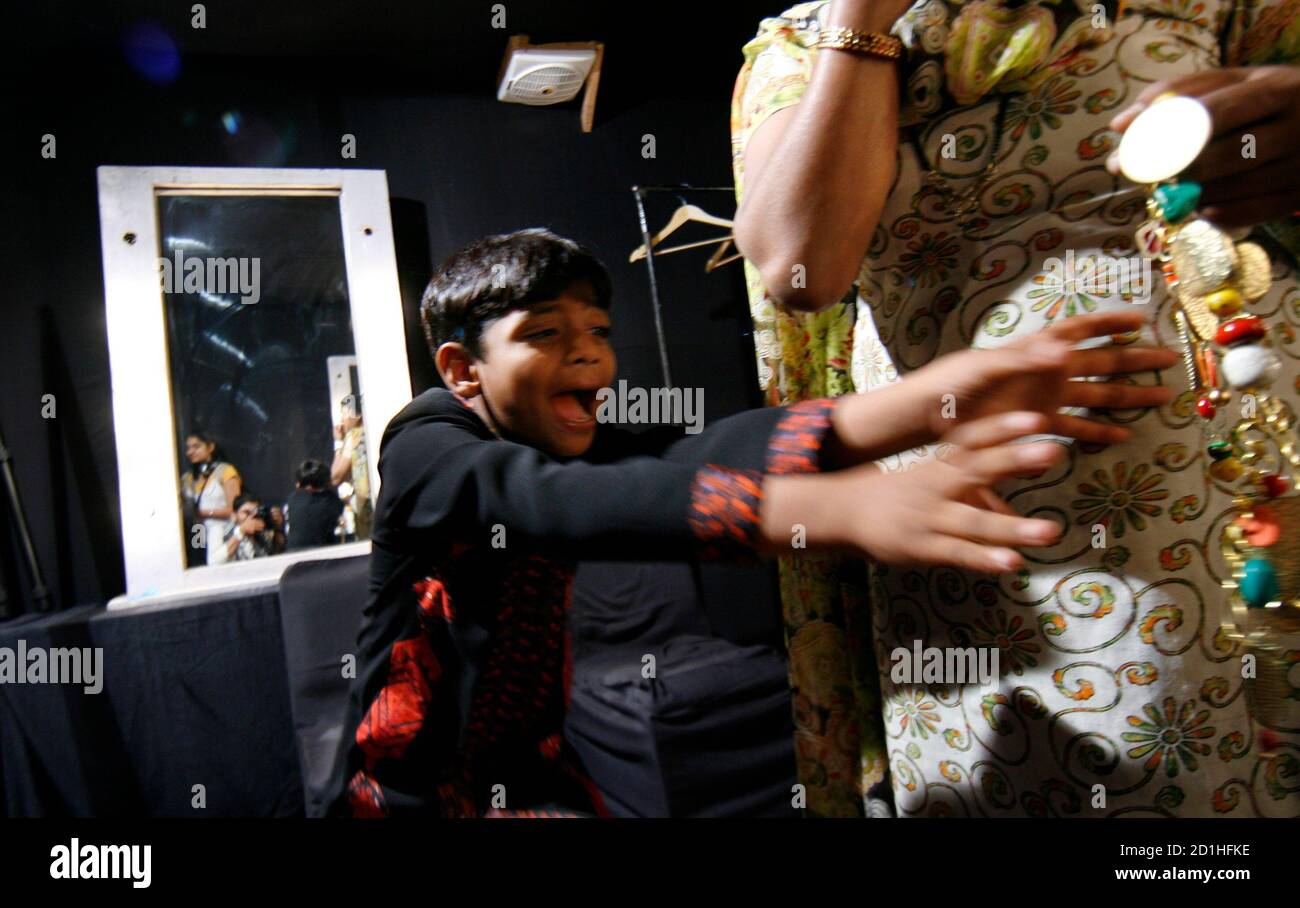 """Azharuddin Ismail, who acted in the film """"Slumdog Millionaire"""", plays with jewellery backstage before the start of the Ashima Leena fashion show on the second day of India Fashion Week in New Delhi March 19, 2009. REUTERS/Adnan Abidi (INDIA FASHION ENTERTAINMENT) Stock Photo"""