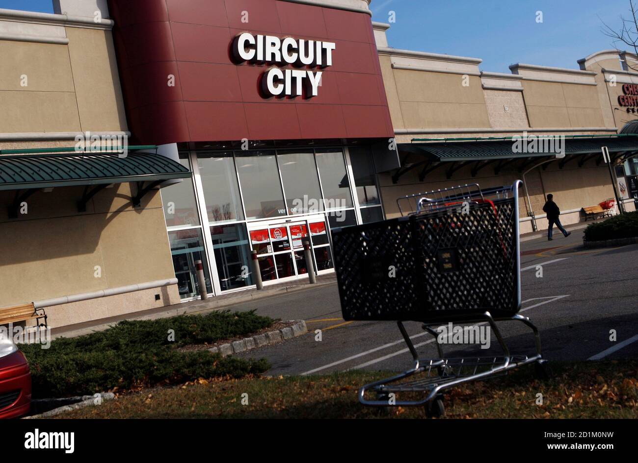 A shopping cart is left at a parking lot while a lone shopper walks in front of the Circut City store in the Paramus Towne Square mall in Paramus, New Jersey, November 18, 2008. Shopping centers, a category that includes strip malls, are doing much worse than that, reporting vacancy rates of 9.4 percent. Larger, enclosed malls are doing better, with vacancy rates of about 3.9 percent. The store closings have come as the U.S. economic downturn forces retailers to scale back expansion plans, close outposts or file for bankruptcy protection. The trend is expected to accelerate as the financial cr Stock Photo