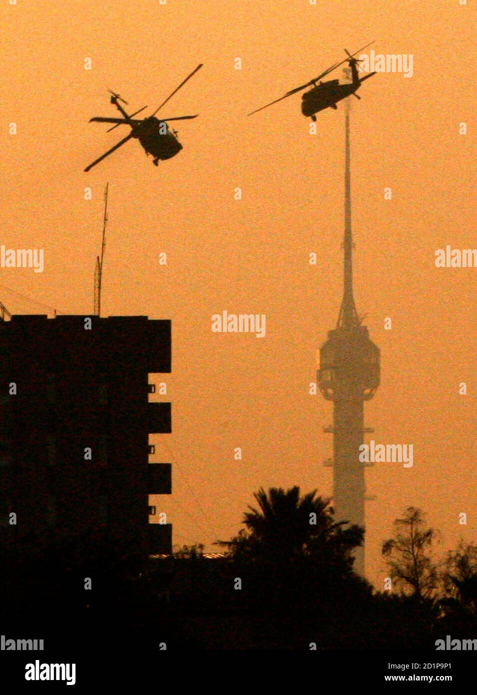 Two U.S. Black Hawk helicopters patrol over Baghdad during sunset November 30, 2006. REUTERS/Nikola Solic     (IRAQ) Stock Photo