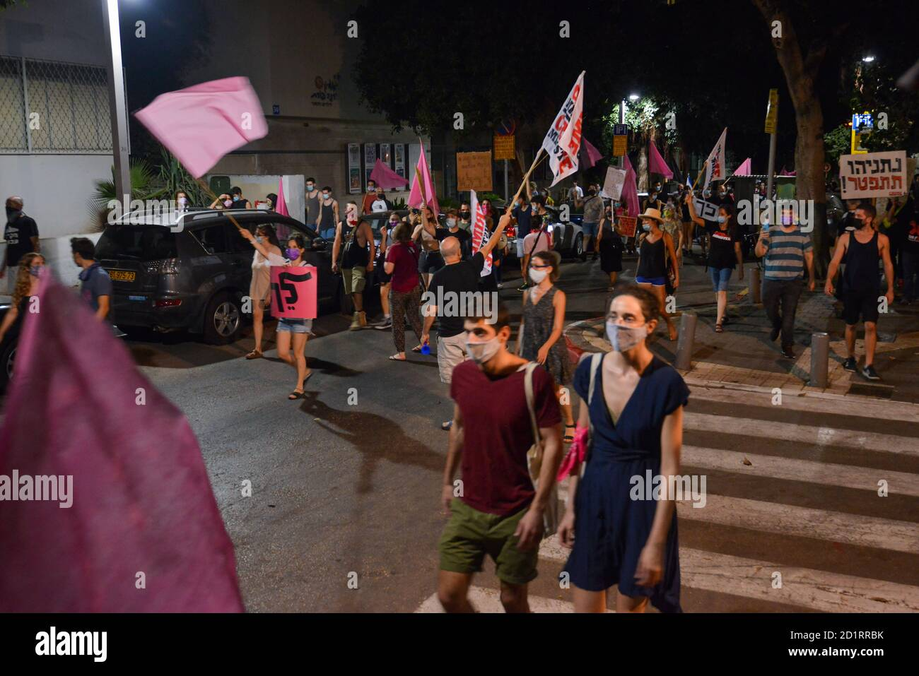 2.10.2020 Tel Aviv, Israel. Protest against Prime minister Netanyahu and second Coronavirus lockdown. Early stages of the protest in which hundreds were marching in Tel Aviv streets calling Bibi Netanyahu to resign. The pink flags symbolize the weakened populations, grace, empathy had become the youth symbol of what they see as the revolution Stock Photo