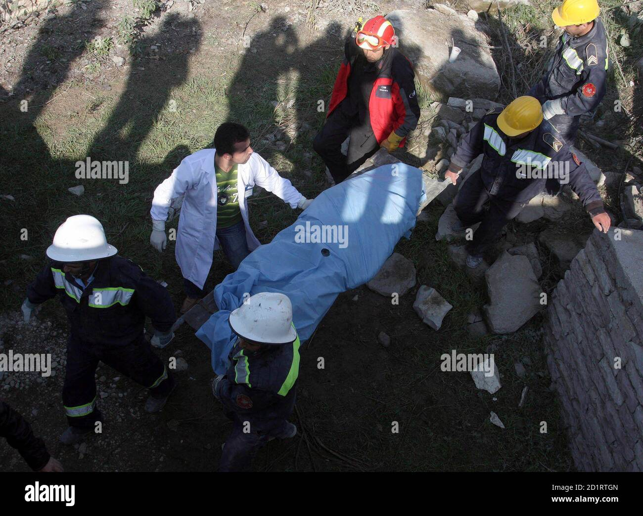 Albanian firefighters carry the body of 65-year-old Parashqevi Zoto after removing her from the rubble of a collapsed apartment building in Gjirokaster, some 250 km (156 miles) south of Tirana near the Greek border, November 10, 2008. Zoto and a young mother and her daughter were trapped when the six-storey building collapsed on Sunday, injuring four people, according to local media.       REUTERS/Arben Celi (ALBANIA) Stock Photo