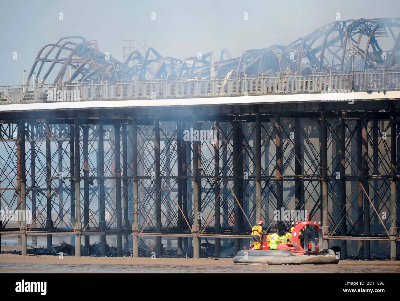 Emergency services workers inspect the Grand Pier at Weston-Super-Mare in south west England July 28, 2008. Firefighters were called to a large blaze that swept through the historic pier at the Somerset seaside resort of Weston-super-Mare on Monday, police said. Flames and thick black smoke engulfed the structure and could be seen from the M5 motorway, several miles from the coast, a fire brigade spokeswoman said.   REUTERS/Toby Melville    (BRITAIN) Stock Photo