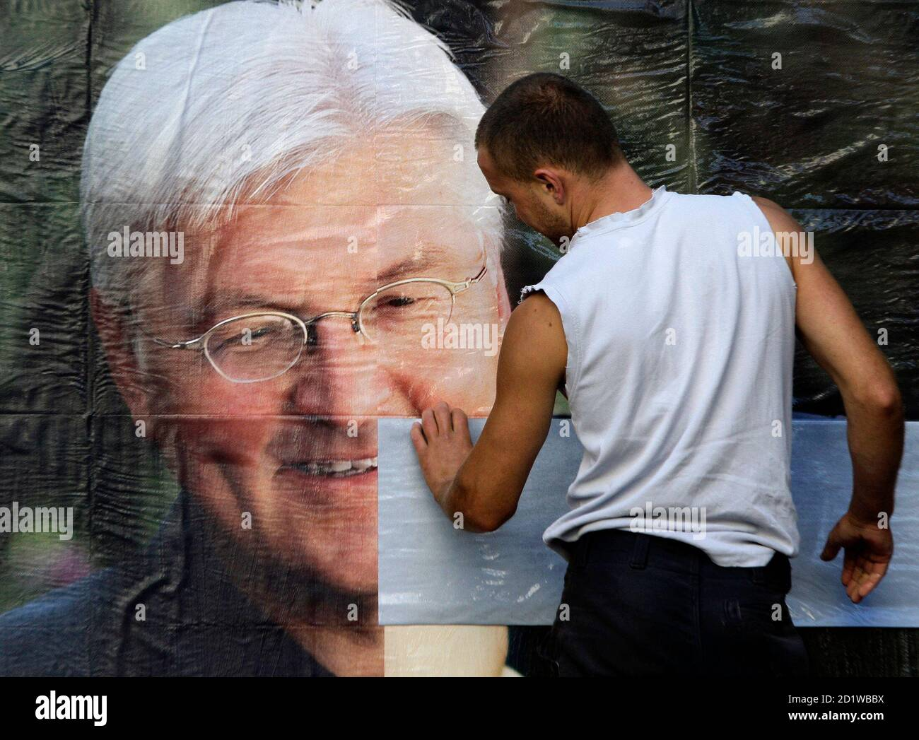 Workers paste up election posters showing German Foreign Minister and candidate for chancellor of Germany's Social Democratic Party (SPD) Frank-Walter Steinmeier in Berlin, August 31, 2009. Senior members of Chancellor Angela Merkel's conservatives warned on Monday that heavy losses in weekend regional votes were a wake up call one month before the German election and called for a more aggressive campaign.  REUTERS/Tobias Schwarz     (GERMANY POLITICS ELECTIONS IMAGES OF THE DAY) Stock Photo