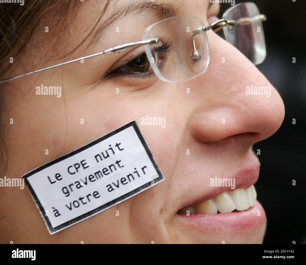 """A French student sticks sign on face which reads """"CPE is harmful to future"""" in protest against the government's new plan for reducing joblessness, in Lille, northern France March 16, 2006. The new job contract, known as the CPE, would allow firms to hire youths under 26 for a two-year trial period before offering them a permanent job. Stock Photo"""