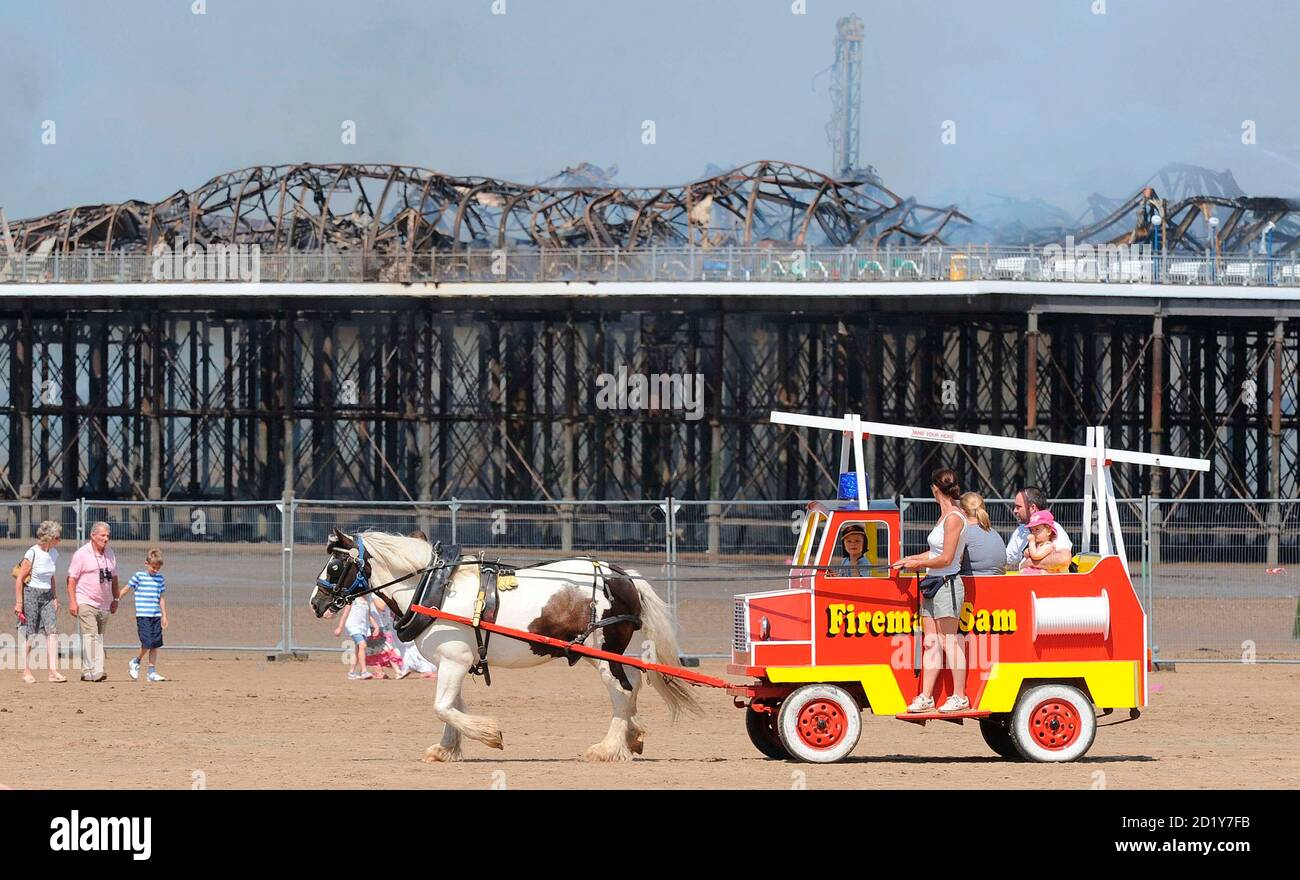 Holiday makers pass the Grand Pier at Weston-Super-Mare in south west England July 28, 2008. Firefighters were called to a large blaze that swept through the historic pier at the Somerset seaside resort of Weston-super-Mare on Monday, police said. Flames and thick black smoke engulfed the structure and could be seen from the M5 motorway, several miles from the coast, a fire brigade spokeswoman said.   REUTERS/Toby Melville    (BRITAIN) Stock Photo
