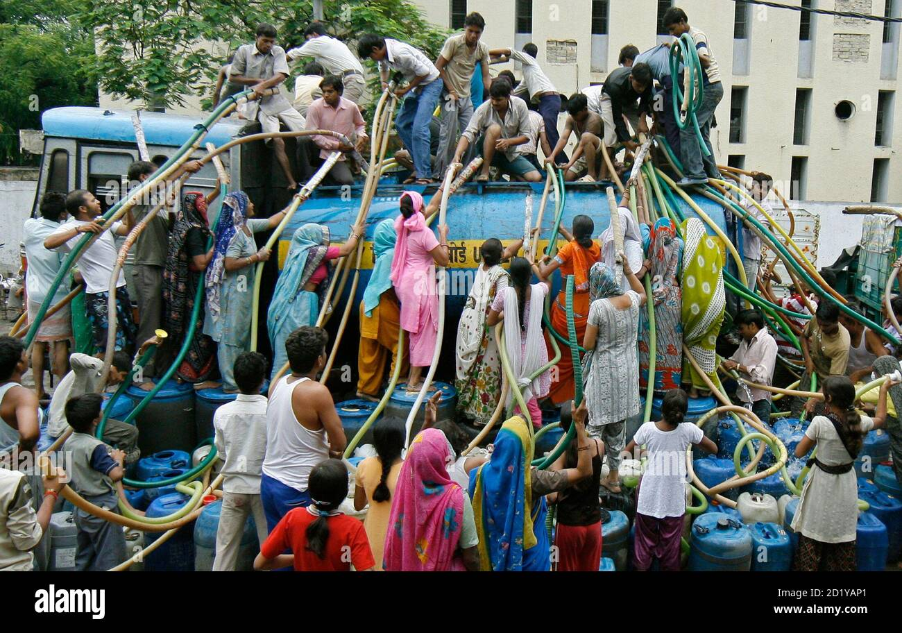 Residents of Sanjay Colony, a residential neighbourhood, crowd around a water tanker provided by the state-run Delhi Jal (water) Board to fill their containers in New Delhi June 30, 2009. Delhi Chief Minister Sheila Dikshit has given directives to tackle the burgeoning water crisis caused by uneven distribution of water in the city according to local media. The board is responsible for supplying water in the capital. REUTERS/Adnan Abidi (INDIA ENVIRONMENT SOCIETY) Stock Photo