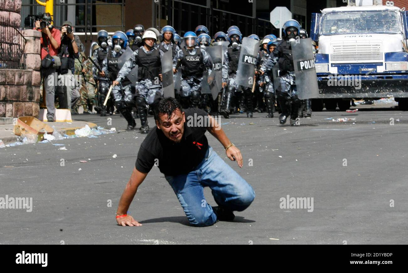 A supporter of Honduras' ousted president Manuel Zelaya reacts as he is hit by tear gas shot by riot police during a demonstration march in downtown Teguciglapa September 23, 2009. Honduran security forces on Wednesday shot tear gas to disperse thousands of supporters of Zelaya, who is sheltering in the Brazilian Embassy in a bid to return to power.  REUTERS/Oswaldo Rivas (HONDURAS POLITICS CONFLICT) Stock Photo