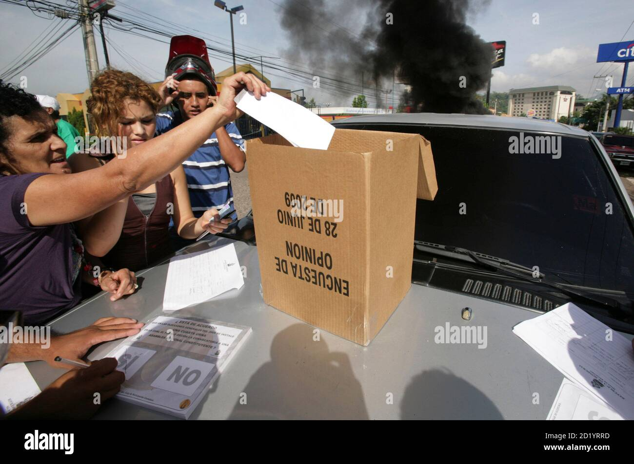 A woman casts a symbolic vote as a show of support for Honduras' President Manuel Zelaya on the streets near the presidential residency in Tegucigalpa June 28, 2009. Witnesses said Zelaya was detained at home by troops in a constitutional crisis over his attempt to win re-election. CNN's Spanish-language channel later quoted Costa Rican officials as saying he was in Costa Rica and seeking political asylum. An unofficial referendum on allowing presidents to serve more than a single four-year term was originally supposed to take place on Sunday. REUTERS/Oswaldo Rivas (HONDURAS POLITICS CONFLICT  Stock Photo