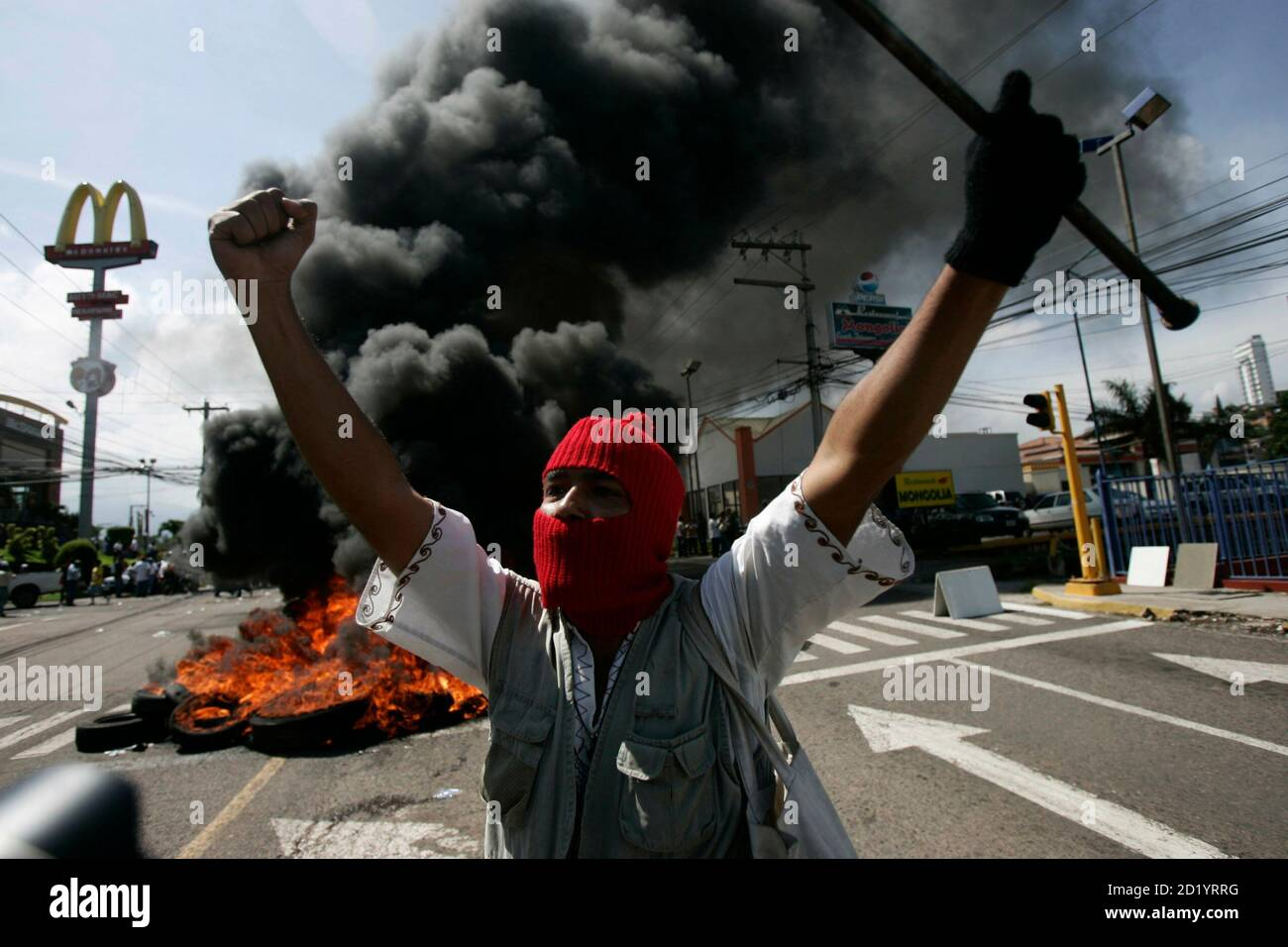 A supporter of Honduras' President Manuel Zelaya demonstrates in front of burning tires outside the presidential residency in Tegucigalpa June 28, 2009. Witnesses said Zelaya was detained at home by troops in a constitutional crisis over his attempt to win re-election. CNN's Spanish-language channel later quoted Costa Rican officials as saying he was in Costa Rica and seeking political asylum. REUTERS/Edgard Garrido (HONDURAS CONFLICT POLITICS IMAGES OF THE DAY) Stock Photo
