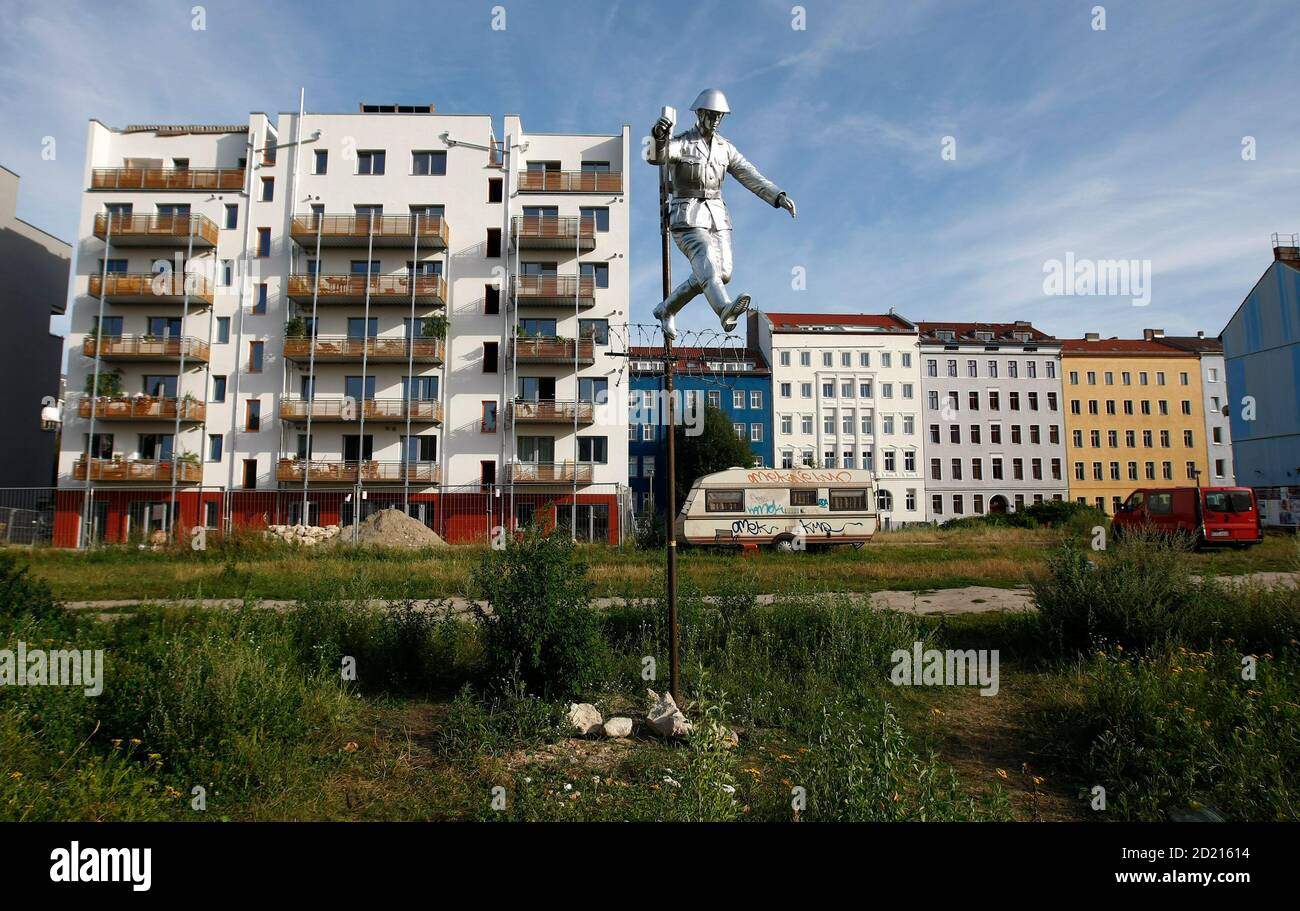 """A view of the sculpture """"Mauerspringer"""" (Walljumper), made by Florian and Michael Brauer and Edward Anders, on the so-called 'death strip', no man's land, of the former Berlin Wall site at the Bernauer Strasse, July 29, 2009. The sculpture is based on the photograph showing former East German border soldier Hans Conrad Schumann jumping over a barbed wire at the Bernauer Strasse on August 15, 1961 to escape from East Berlin to West Berlin.       REUTERS/Fabrizio Bensch (GERMANY POLITICS CITYSCAPE ANNIVERSARY) Stock Photo"""