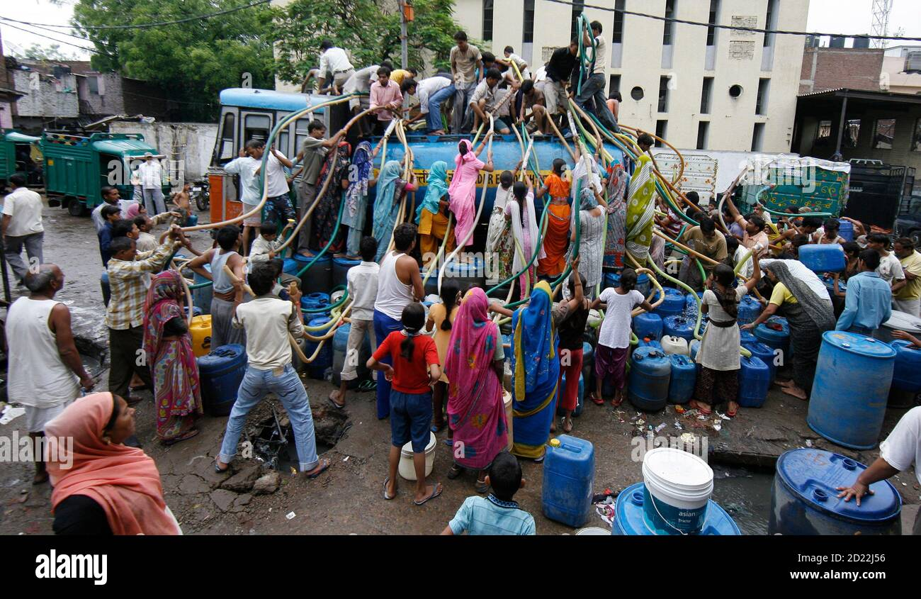 Residents of Sanjay Colony, a residential neighbourhood, crowd around a water tanker provided by the state-run Delhi Jal (water) Board to fill their containers in New Delhi June 30, 2009. Delhi Chief Minister Sheila Dikshit has given directives to tackle the burgeoning water crisis caused by uneven distribution of water in the city according to local media. The board is responsible for supplying water in the capital. REUTERS/Adnan Abidi (INDIA SOCIETY) Stock Photo