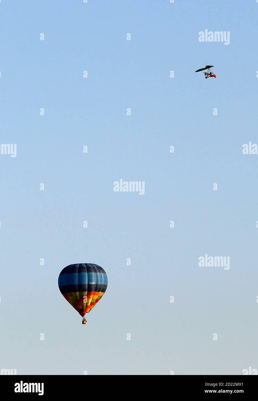 An ultralight aircraft flies near a hot air balloon over Alessandria May 22, 2010.   REUTERS/Alessandro Bianchi   (ITALY - Tags: SOCIETY TRANSPORT) Stock Photo