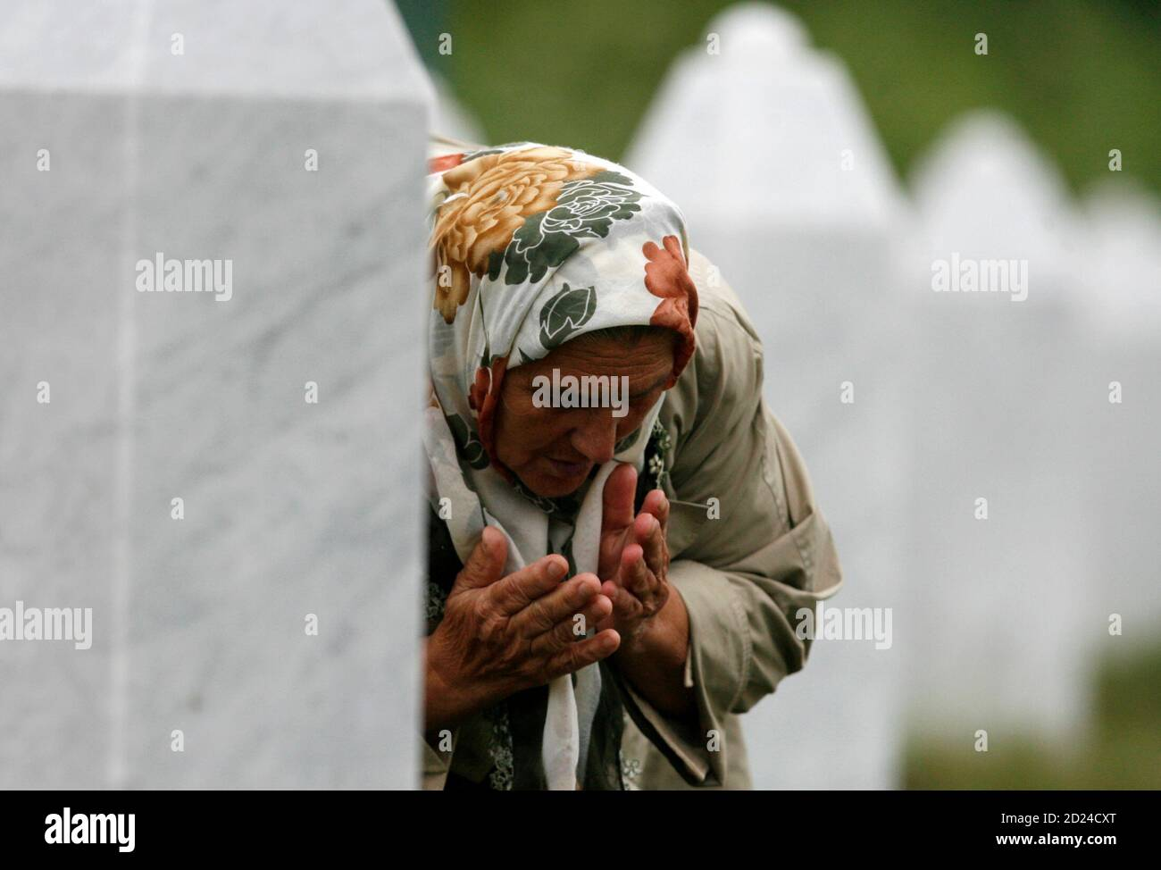 A Bosnian woman who lost a relative in the 1995 Srebrenica massacre prays inside memorial cemetery Potocari near Srebrenica in eastern Bosnia July 22, 2008, after  Bosnian Serb wartime leader Radovan Karadzic's arrest in Belgrade. Karadzic, wanted for genocide and crimes during the Bosnian war, was arrested near Belgrade after 11 years on the run, in disguise and working as a doctor. Karadzic's arrest was one of the main conditions of Serbian progress towards European Union membership and may be enough to secure Serbia closer ties with the EU and possibly the status of membership candidate sta Stock Photo