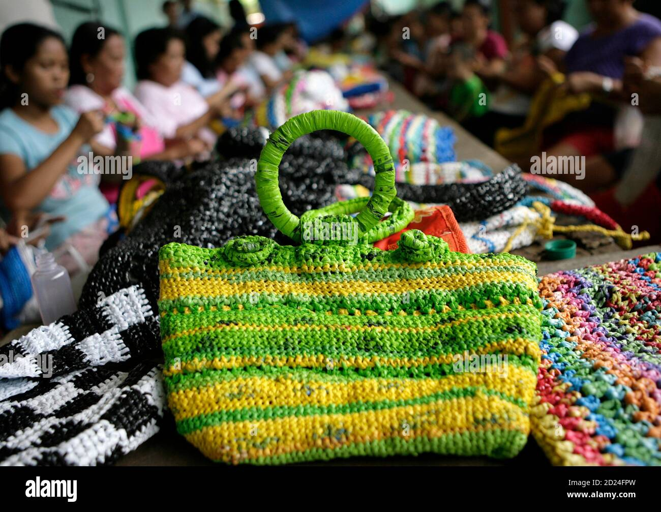 women crochet bags made from recycled plastic bags in manila june 9 2009 women in poor areas of manila have been trained by a non government organization to crochet bags totes hats and other accessories using recycled plastic bags and sell them for between 500 to 1500 pesos 10 30 reuterscheryl ravelo philippines society environment 2D24FPW